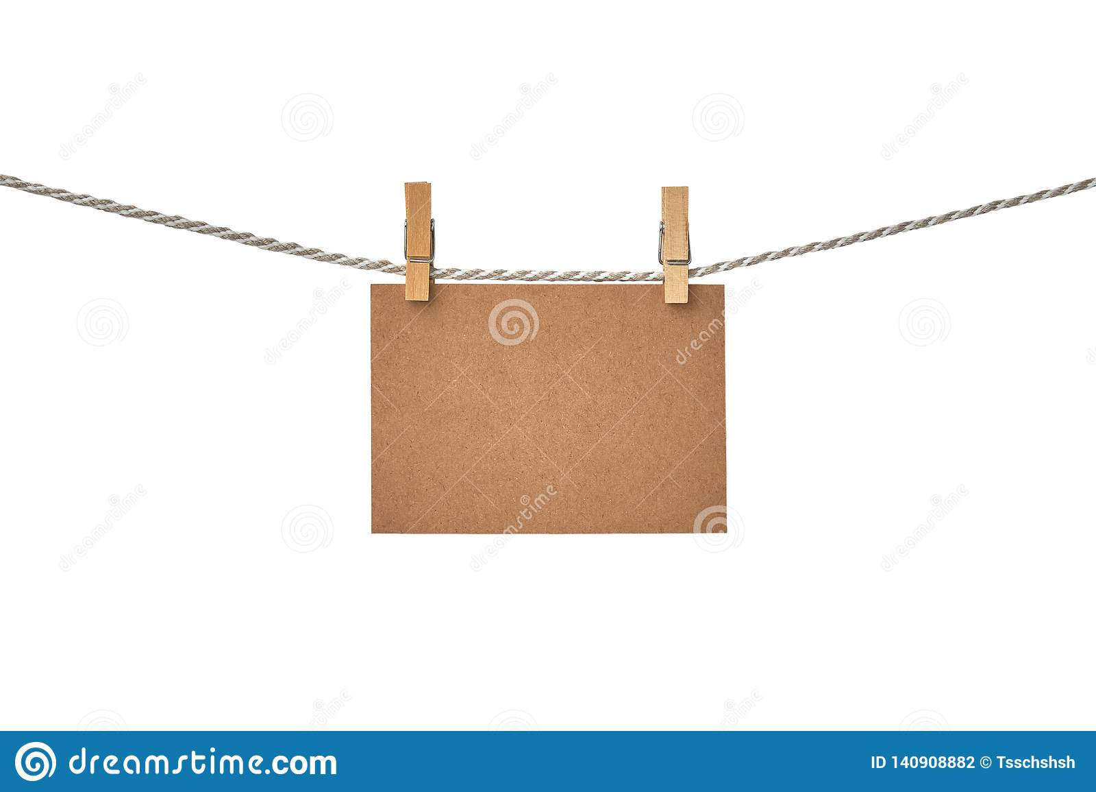 Carte vierge de papier de métier accrochant sur la corde à linge sur le fond blanc