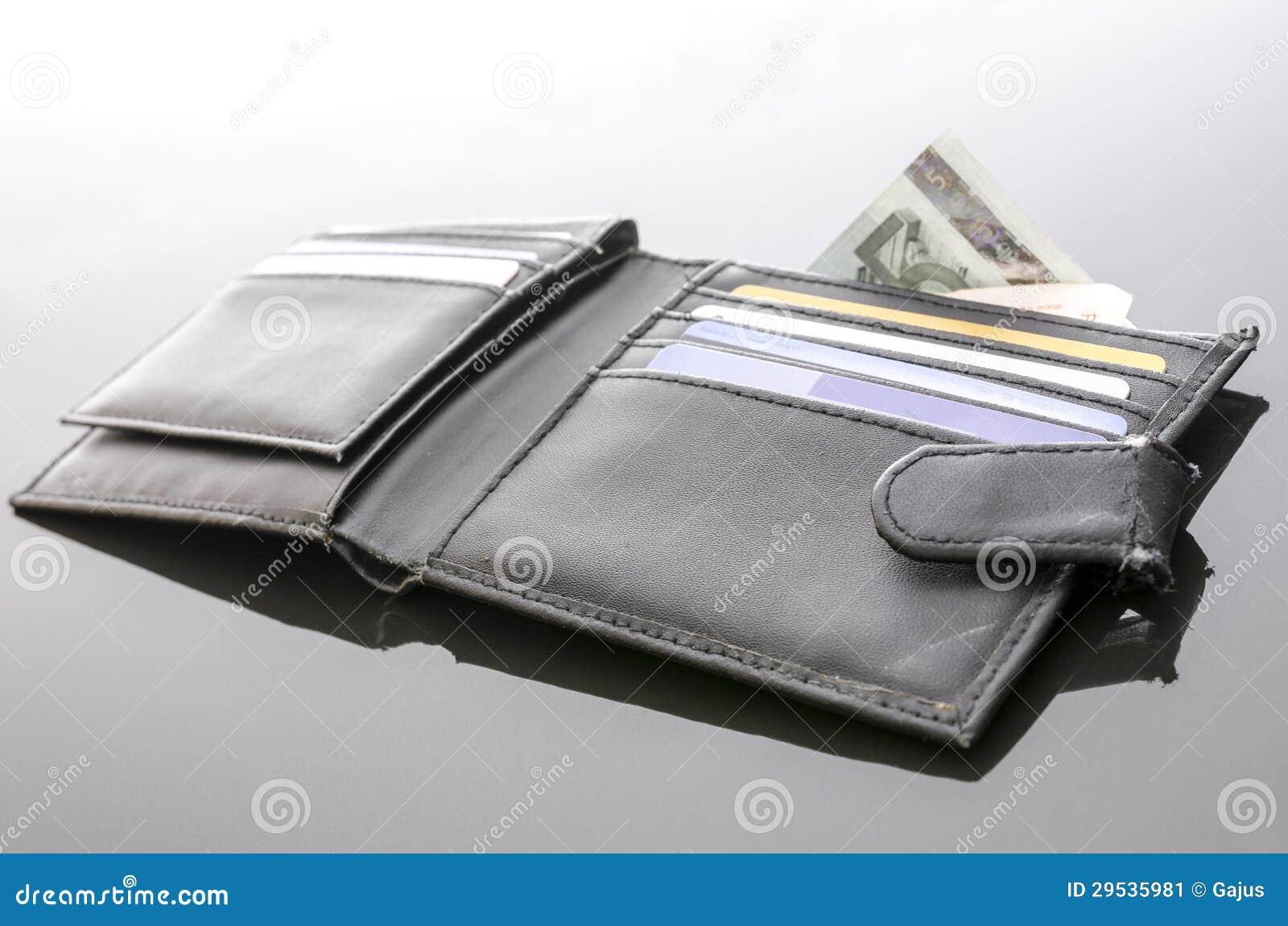 Carteira aberta velha com os cartões do dinheiro e de crédito