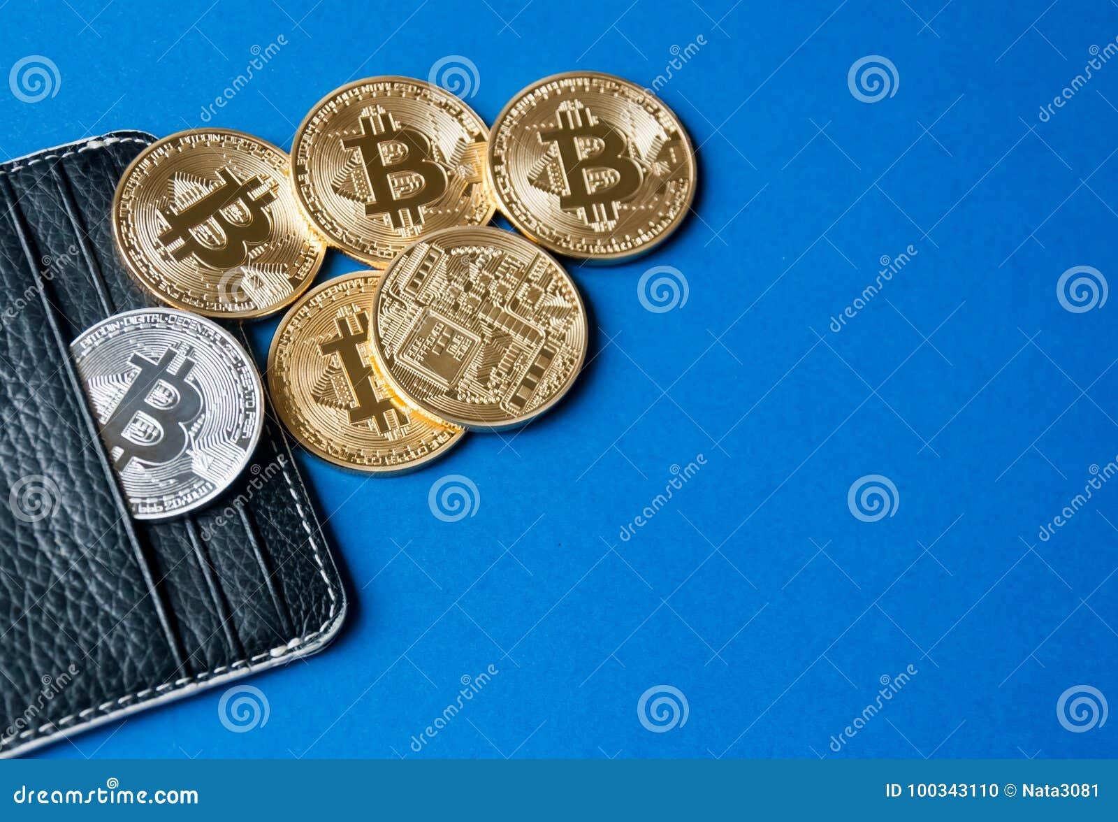 Carteira de couro preta em um fundo azul com diversos ouro e moedas de prata dos bitcoins que caem fora de seus bolsos