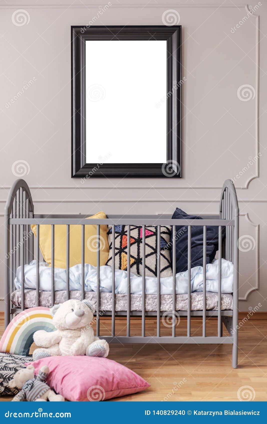 Cartel de la maqueta en marco negro en la pared gris del interior del sitio del bebé con el pesebre con las almohadas, visión ver