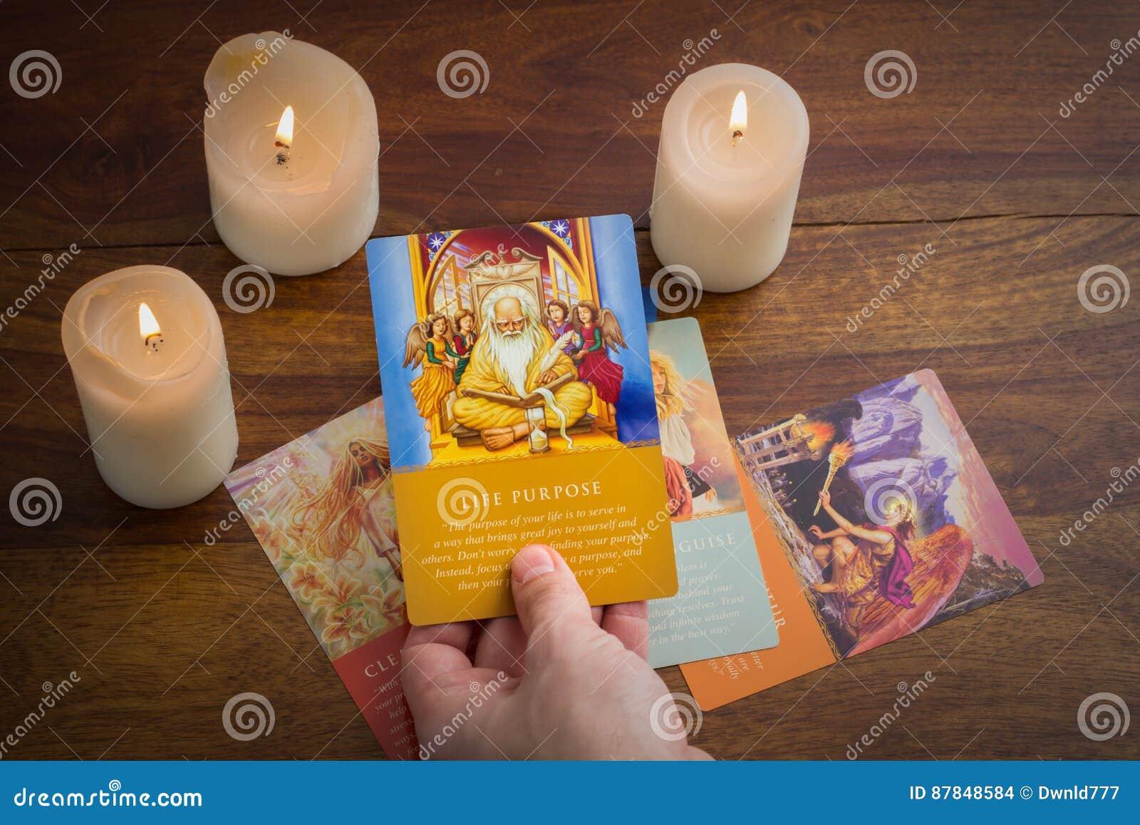 Cartes de tarot et bougie brûlante sur la table en bois