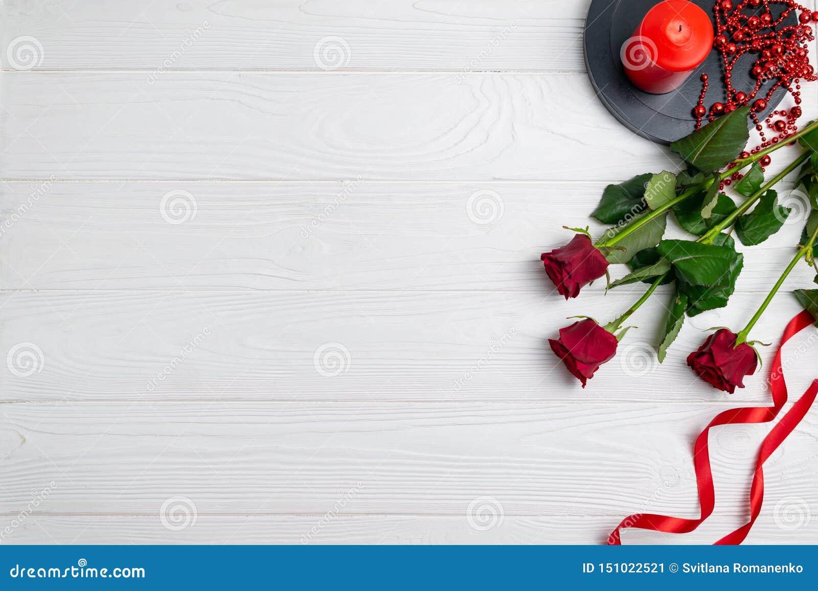 Cartolina d auguri o composizione nel fondo con le rose rosse e candela con spazio per testo