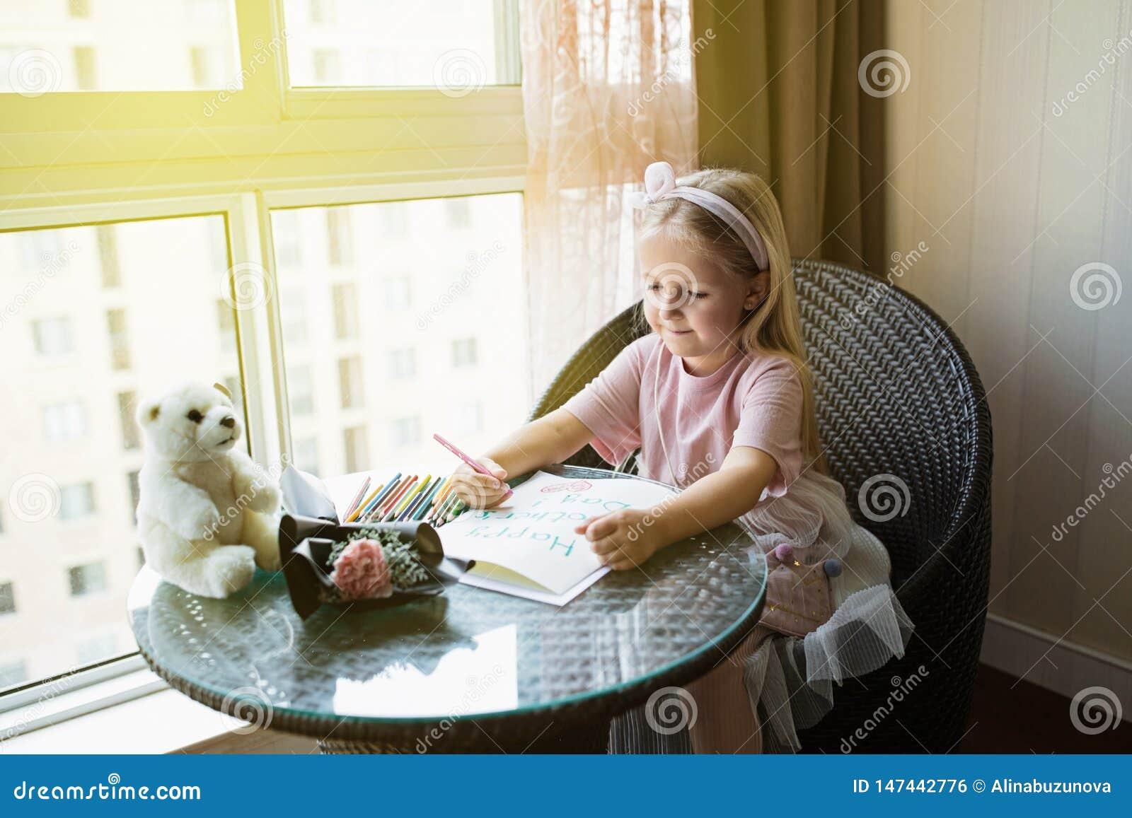 Cartolina della pittura della figlia del bambino per la mamma Ragazza che si siede a casa sulla tavola, fiore rosa dopo di menzog