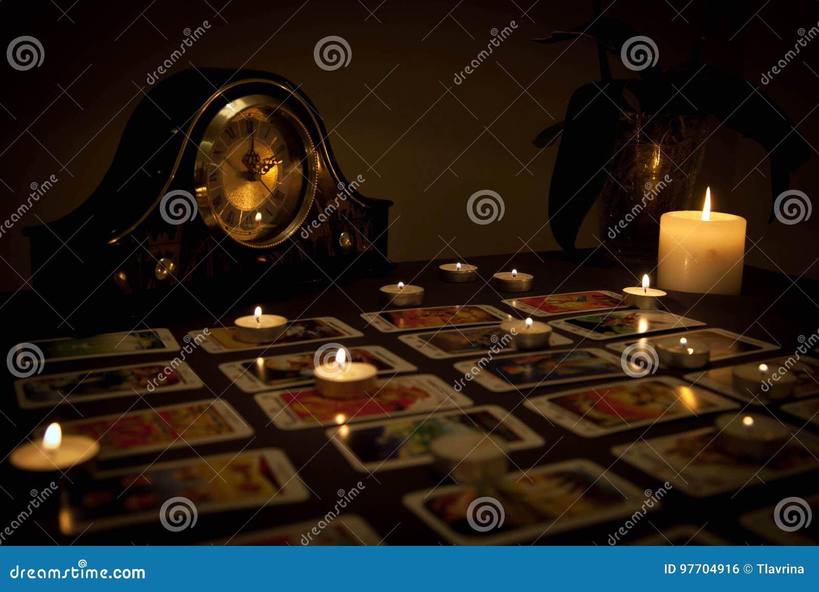 Cartomancie mystique avec les bougies et les cartes mises le feu de jouer dans d