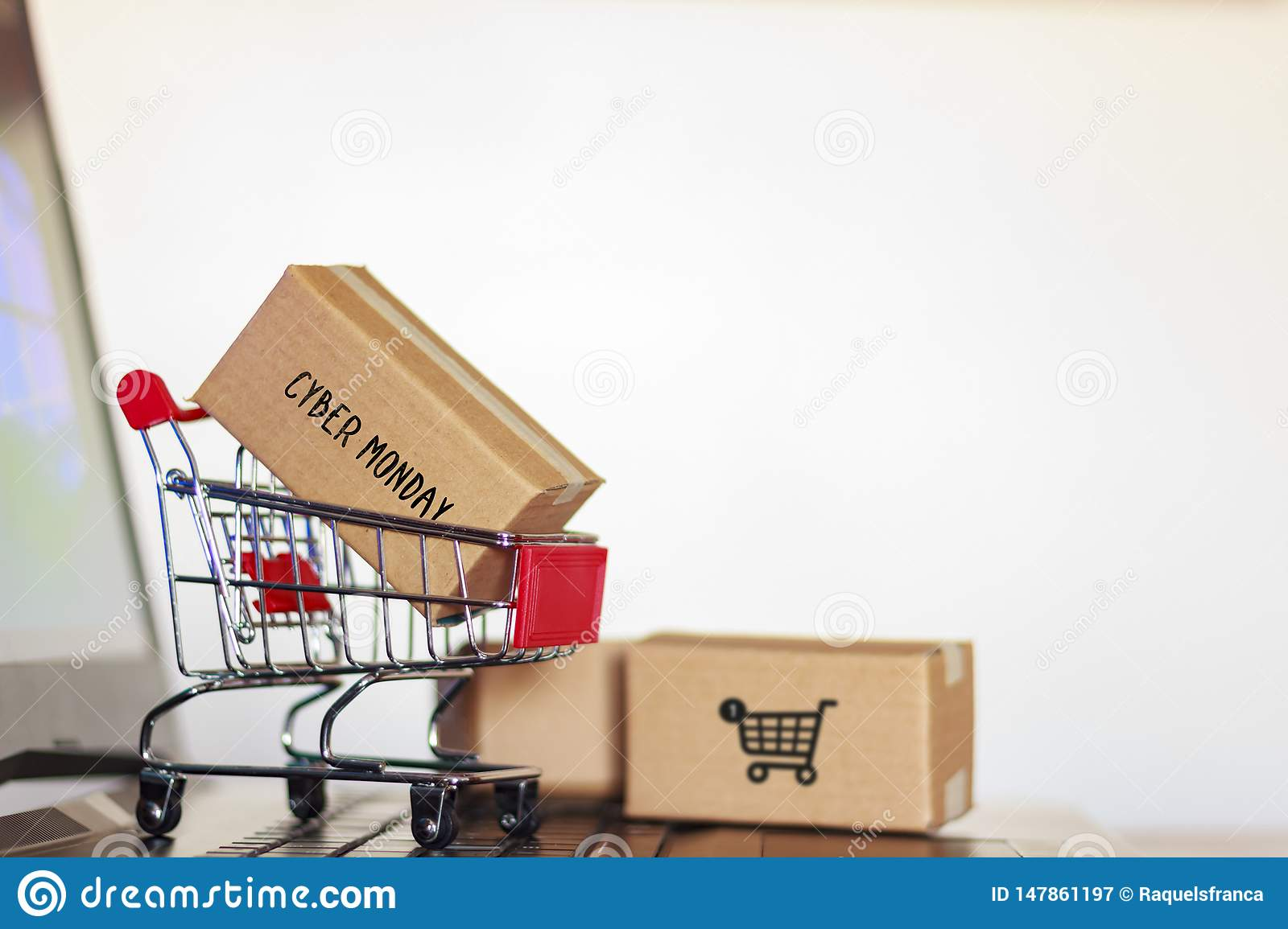 Carton box with cyber monday word and shopping cart on computer. Online shopping, e-commerce concept