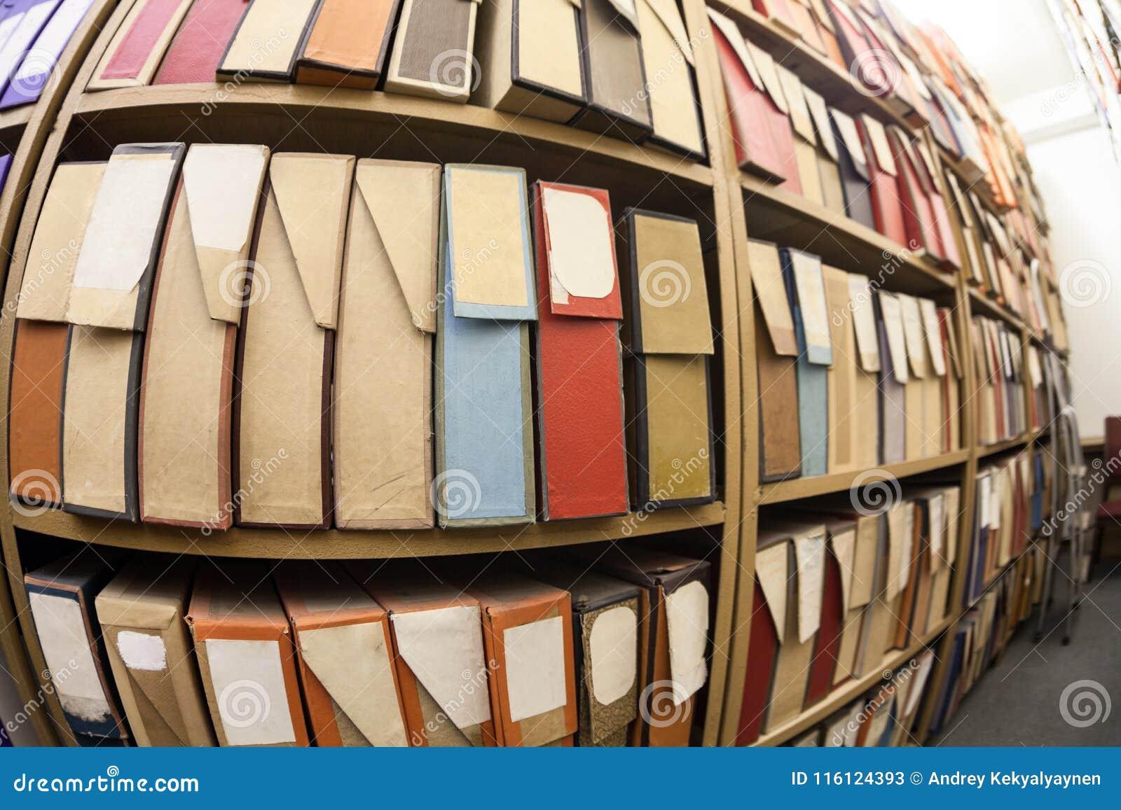 Cartonnez les boîtes pour les documents sur papier, la documentation et les disques se tenant sur des étagères dans les archives