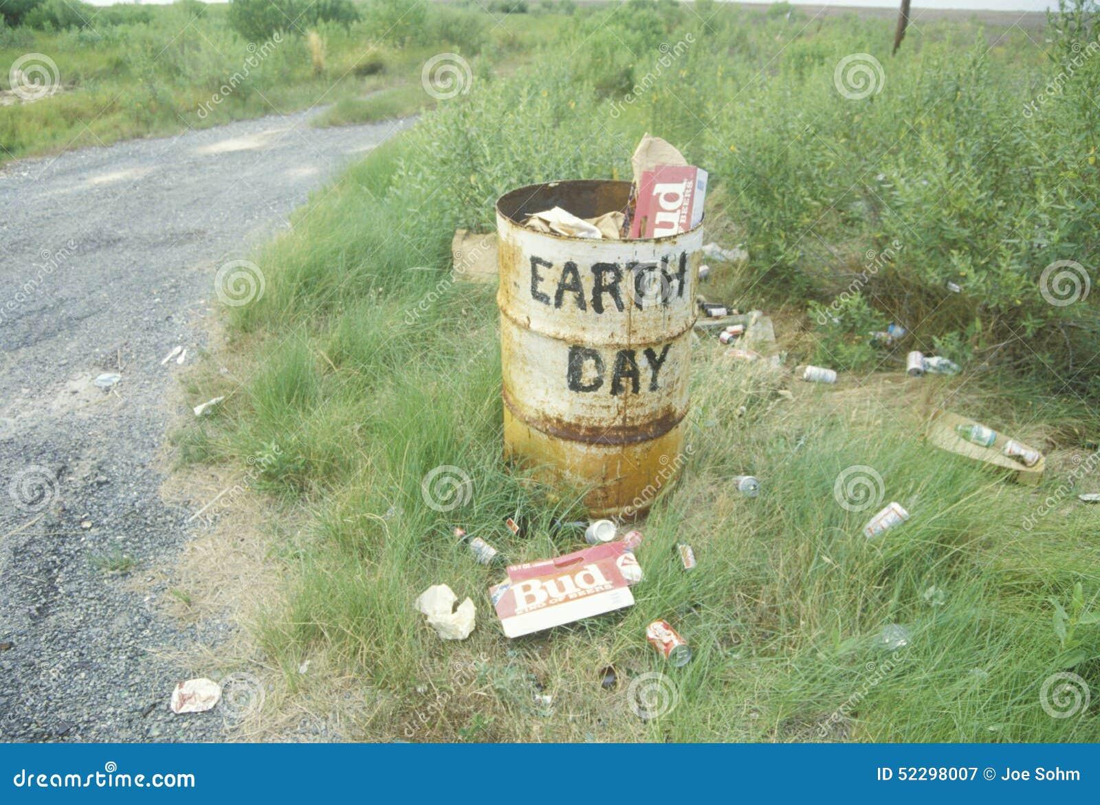 Cartons de bière de carton au sol à côté d une poubelle avec le ?Earth Day? de mots peint de son côté