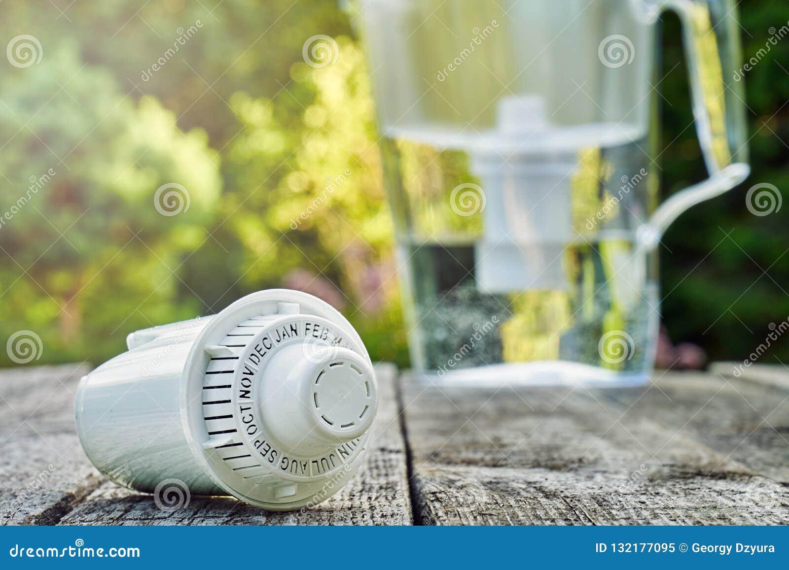 Cartouche remplaçable et une cruche de filtre d eau sur les conseils en bois dans le jardin d été