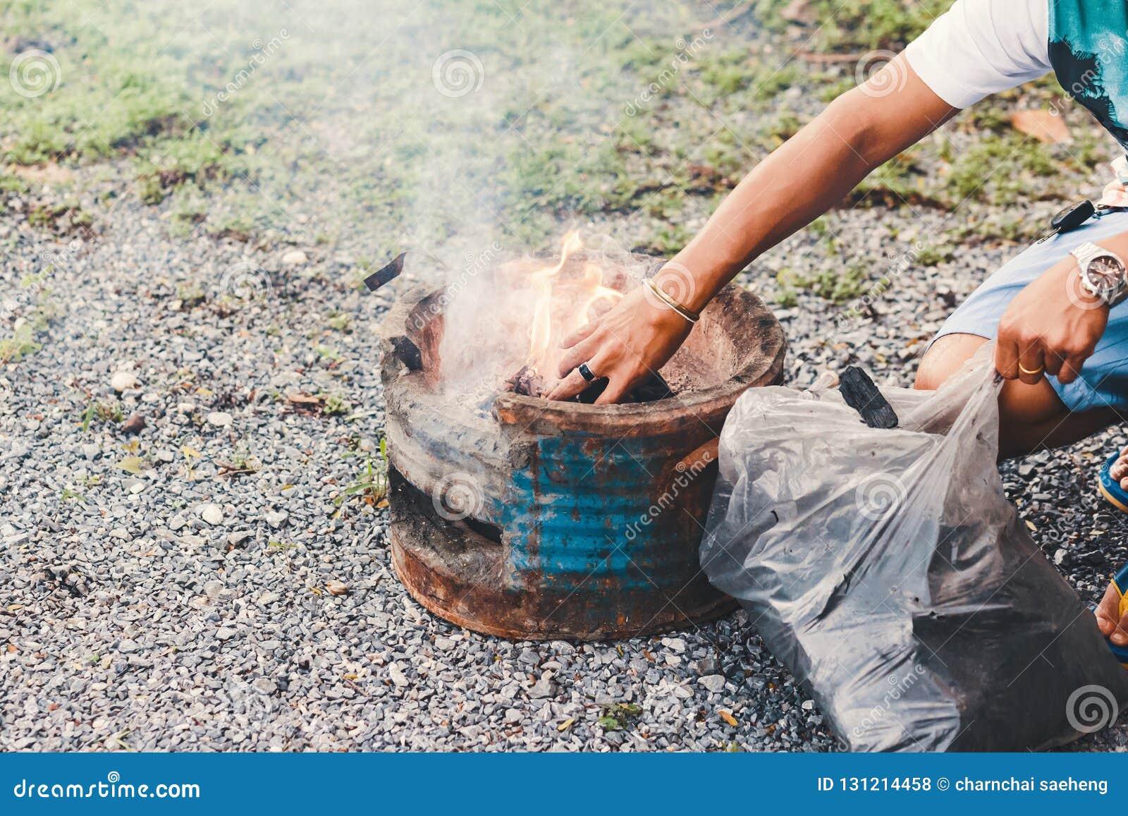 Carvão amassado do carvão vegetal da suficiência do homem de Hans ao carvão vegetal flamejante quente no fogão da grade do BBQ Ca