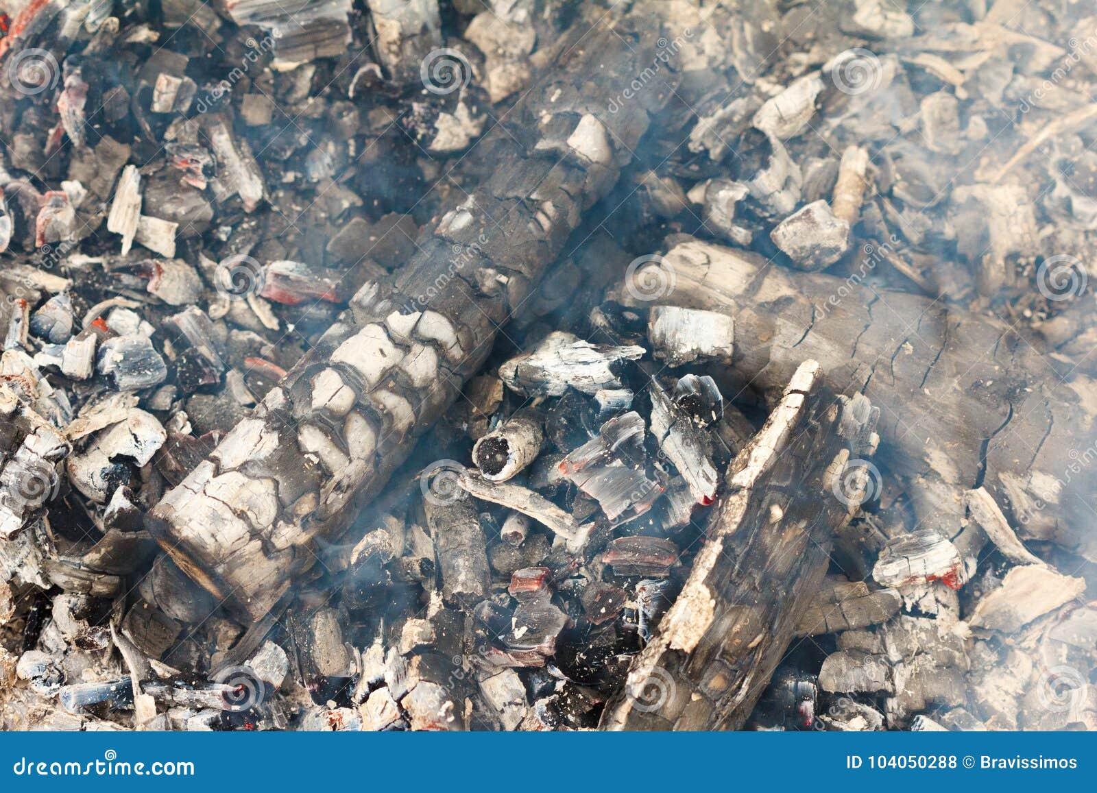 Carvões de incandescência vermelhos do fogo com fumo