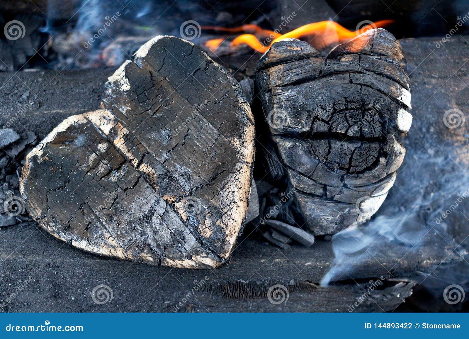 Carv?es quentes e madeiras ardentes sob a forma do cora??o humano Incandesc?ncia e carv?o vegetal flamejante, fogo vermelho brilh