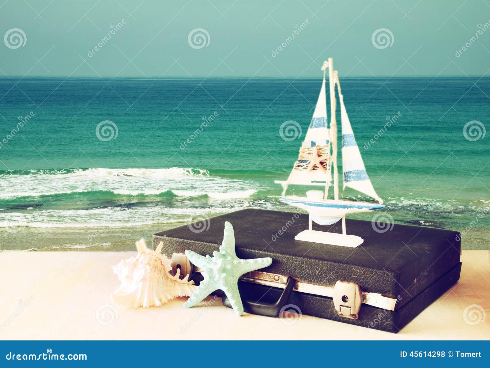 Cas de vintage avec le vieux jouet de bateau et étoiles de mer devant le paysage marin concept de course Image filtrée