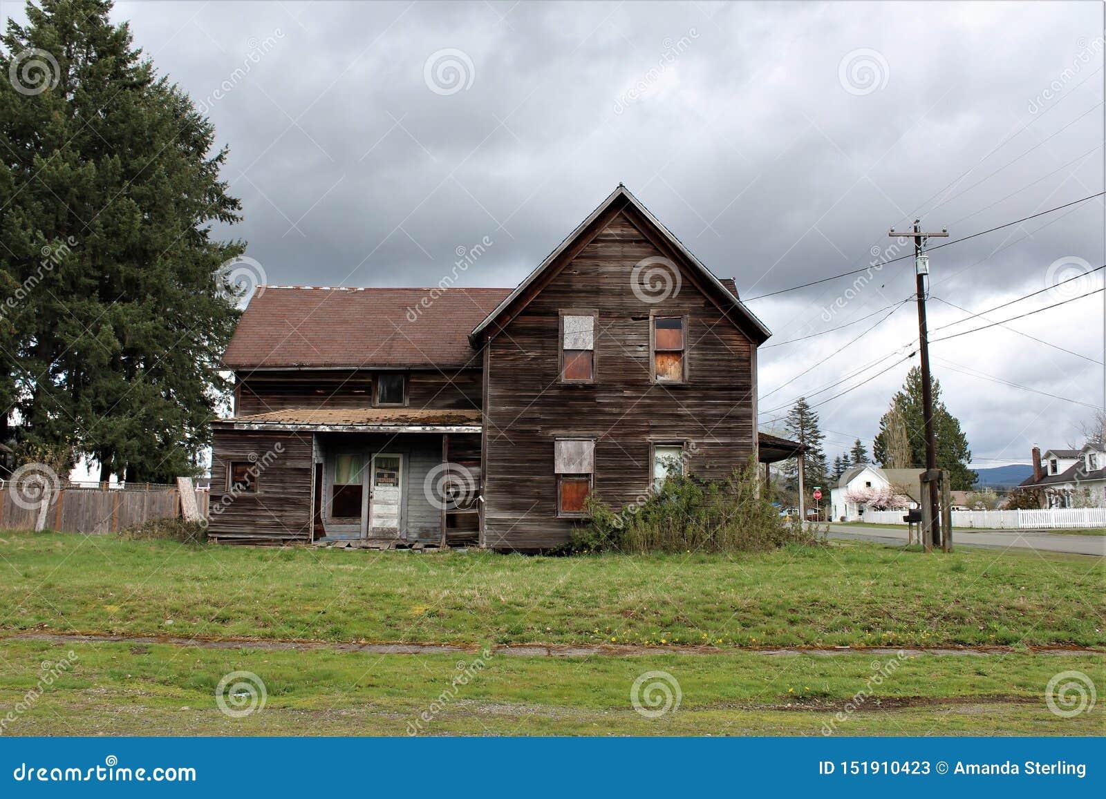 Casa abandonada em quedas do granito, opinião lateral de WA com um arco concreto no jardim da frente