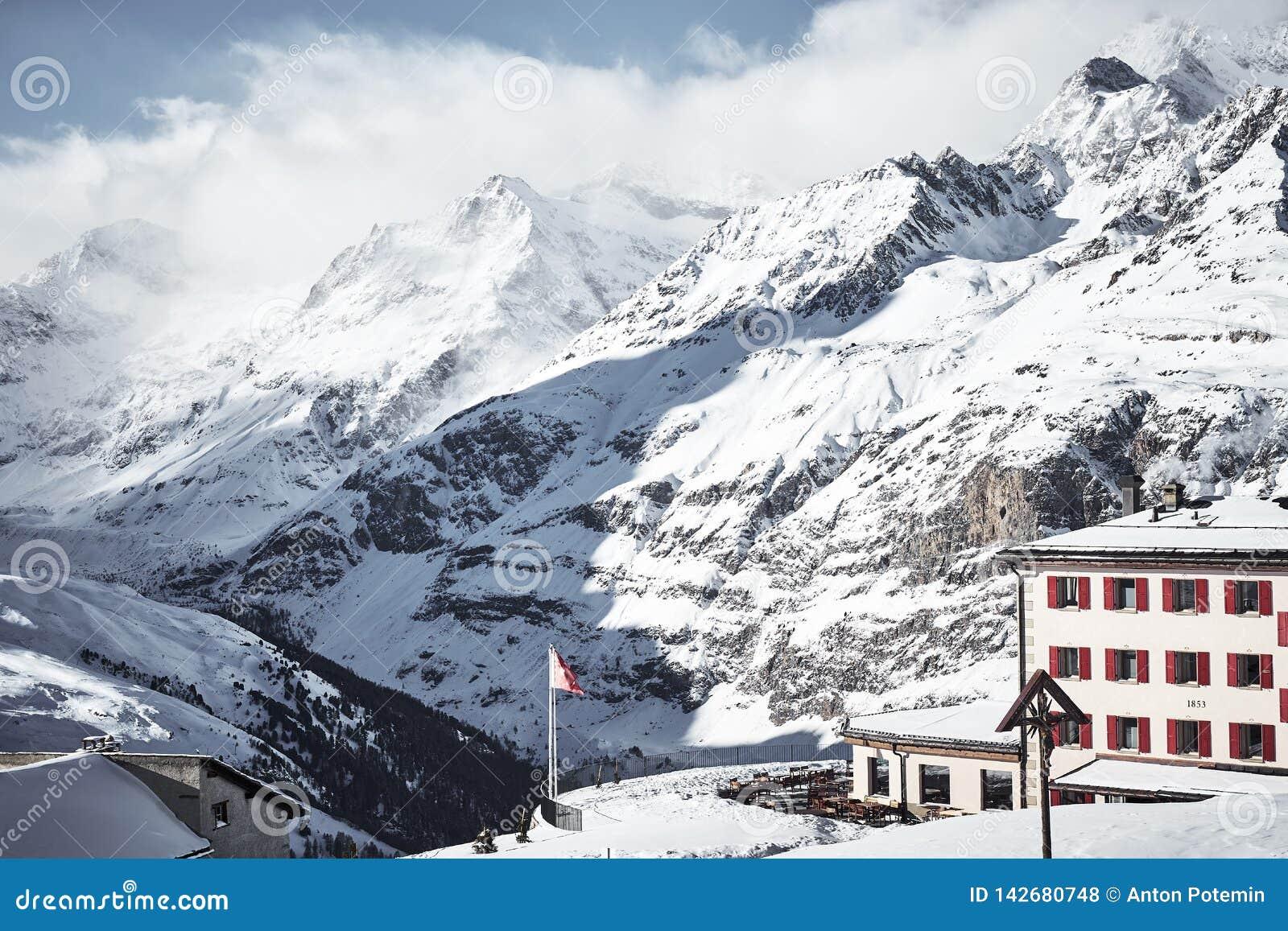 Casa alpina nas montanhas altas cobertas por nuvens