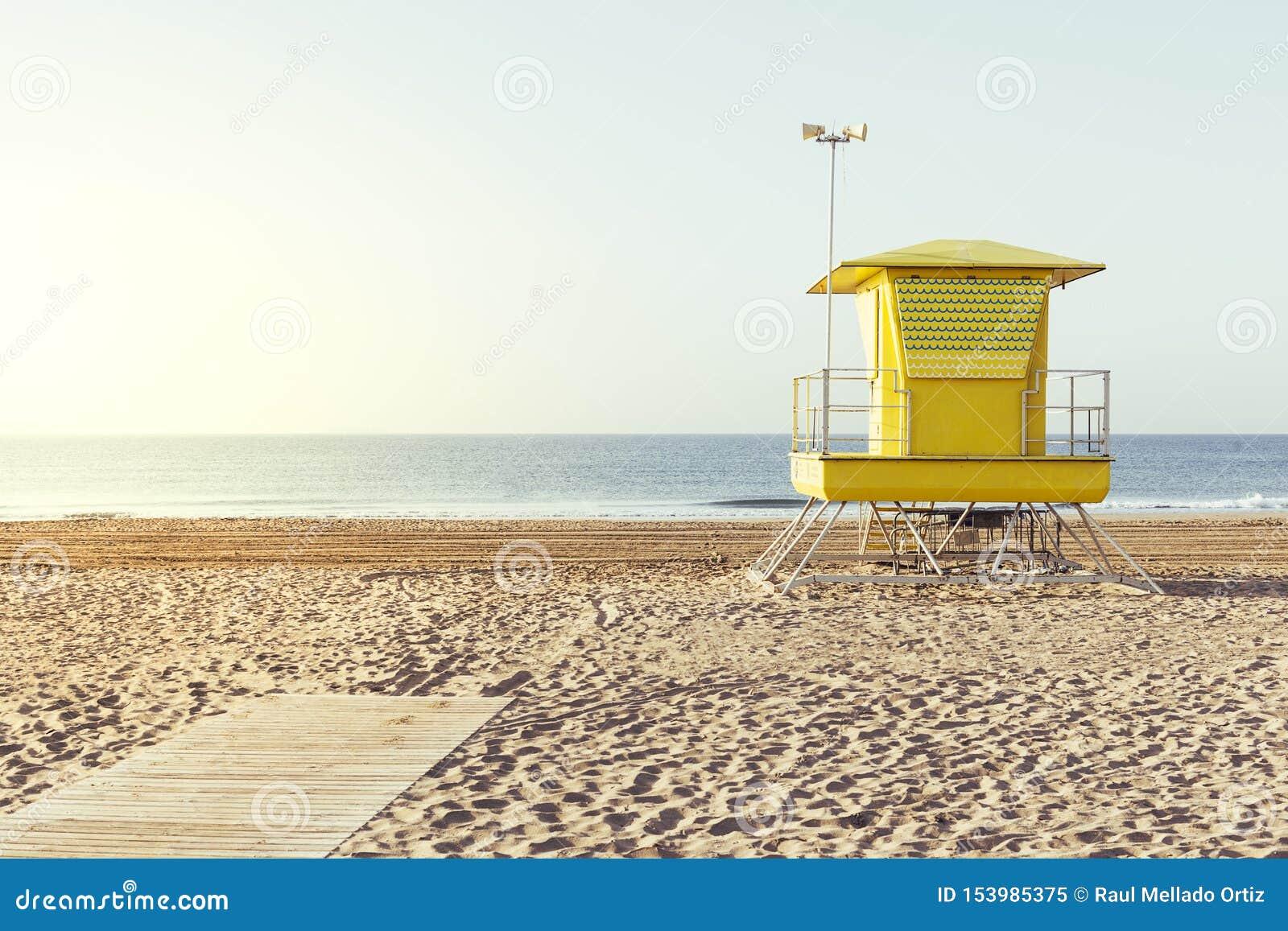 Casa amarilla del salvavidas en la playa