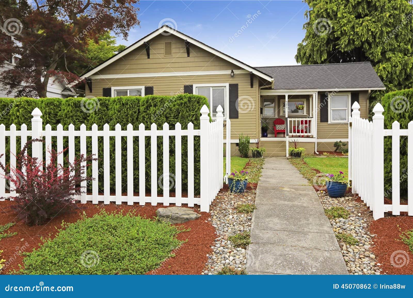 Casa americana exterior con la cerca de madera blanca foto for Casa de madera con jardin