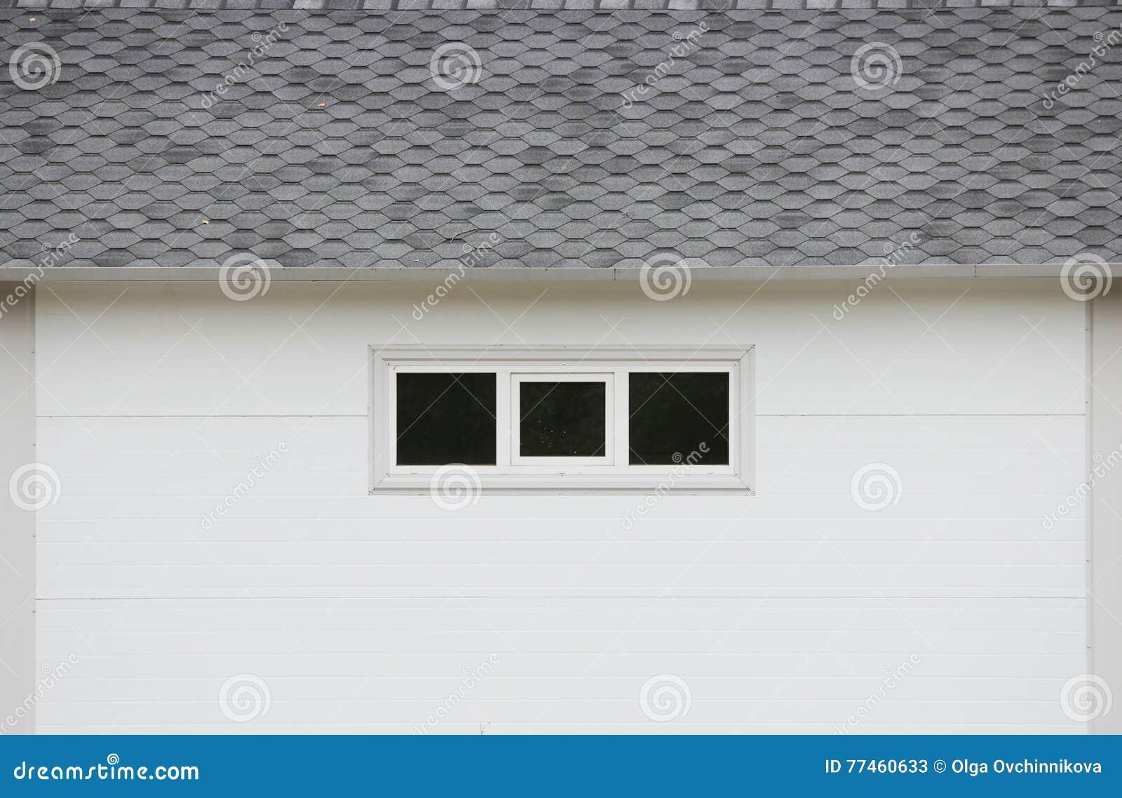 A casa branca da textura da parede, janelas escuras, cinza flexível telha o fundo