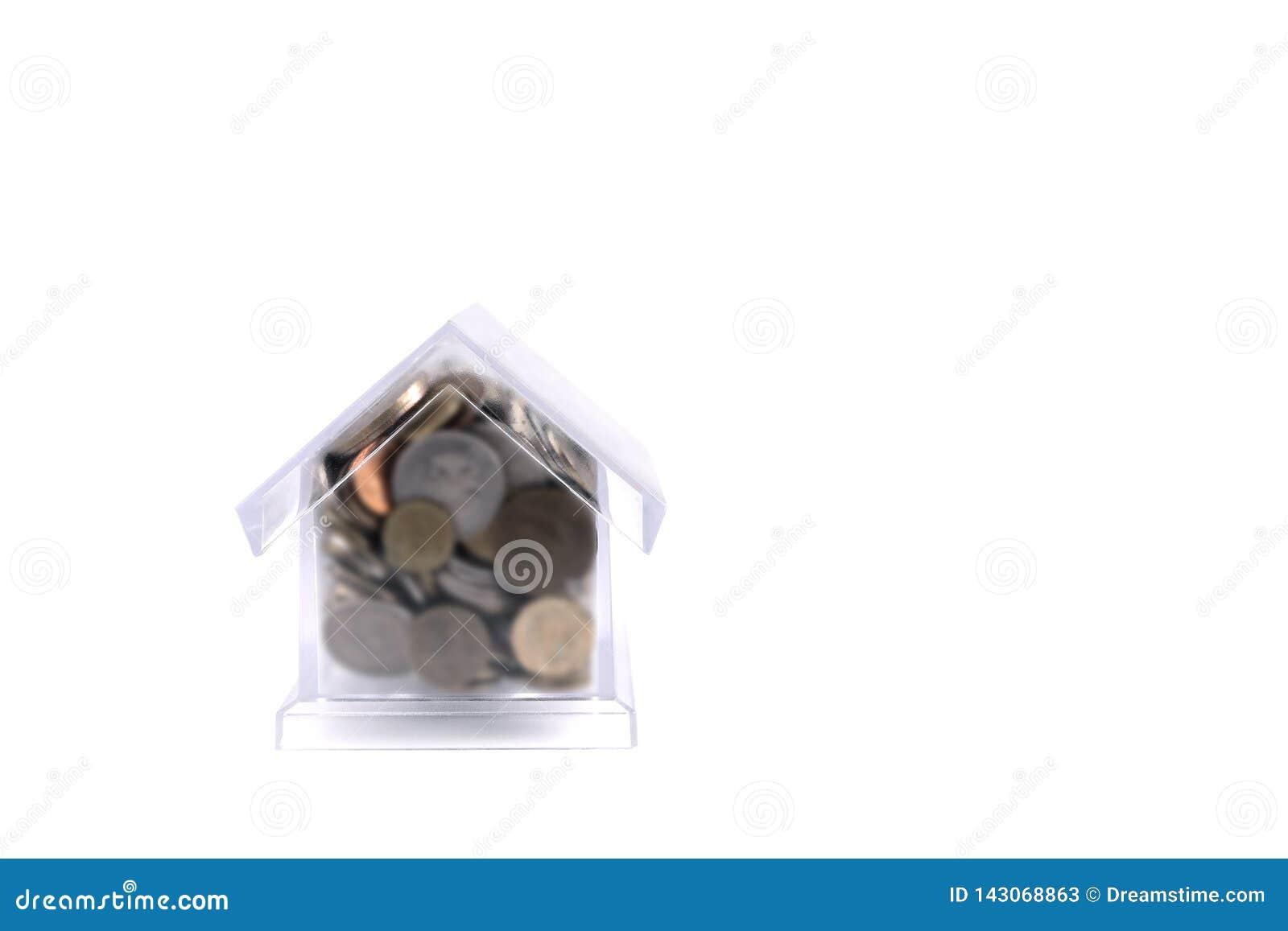 Casa-cerdo con un tubo Casa plástica transparente en un fondo blanco En las monedas del metal de la hucha de diferente
