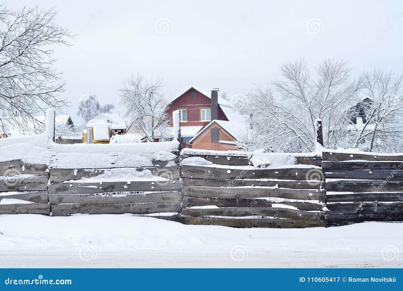 Casa com a terra e as construções, cobertas com a neve, a vista atrás da cerca Composição, fundo