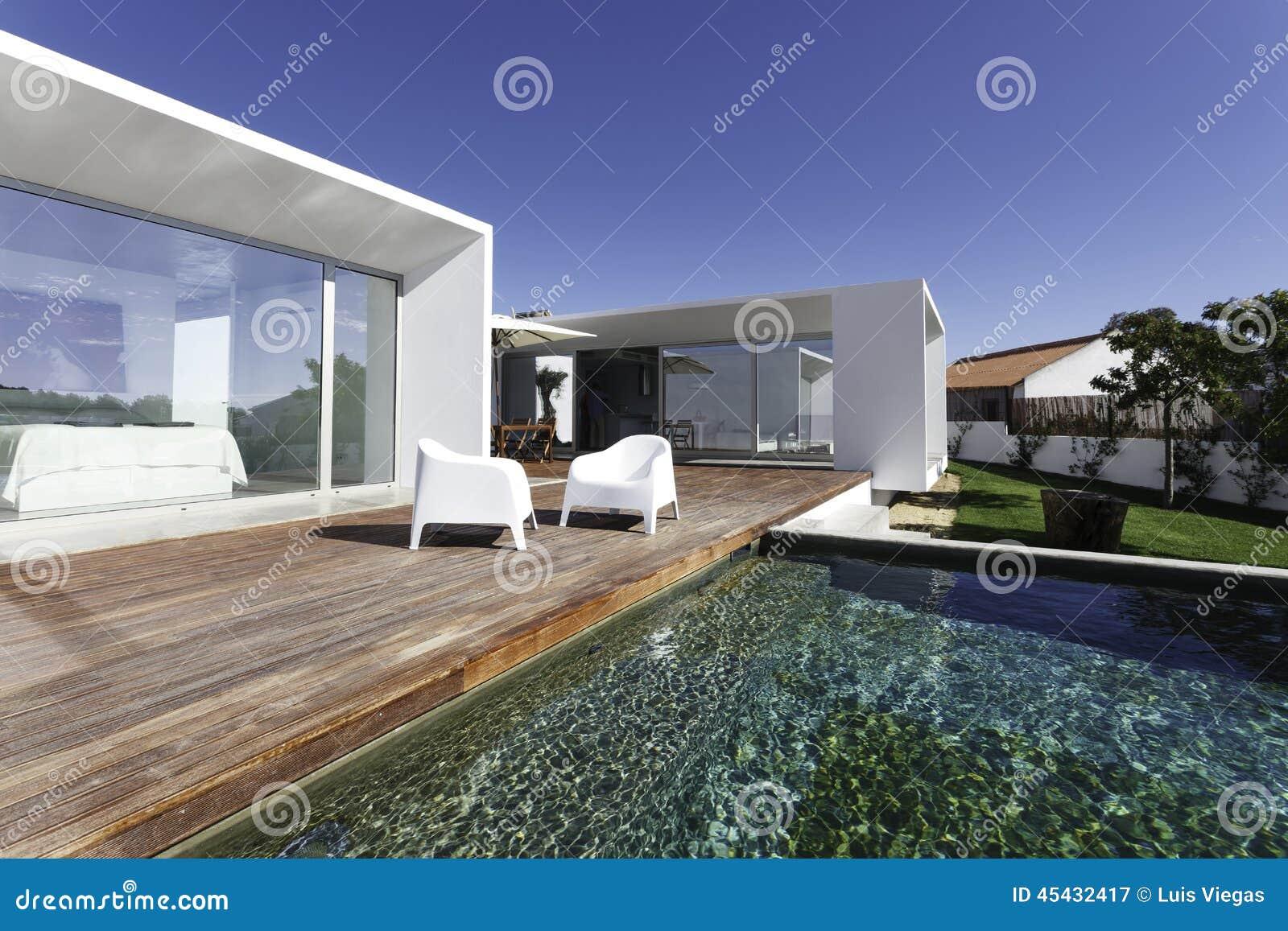 Casa con la piscina del jard n y la cubierta de madera for Casas con jardin y piscina