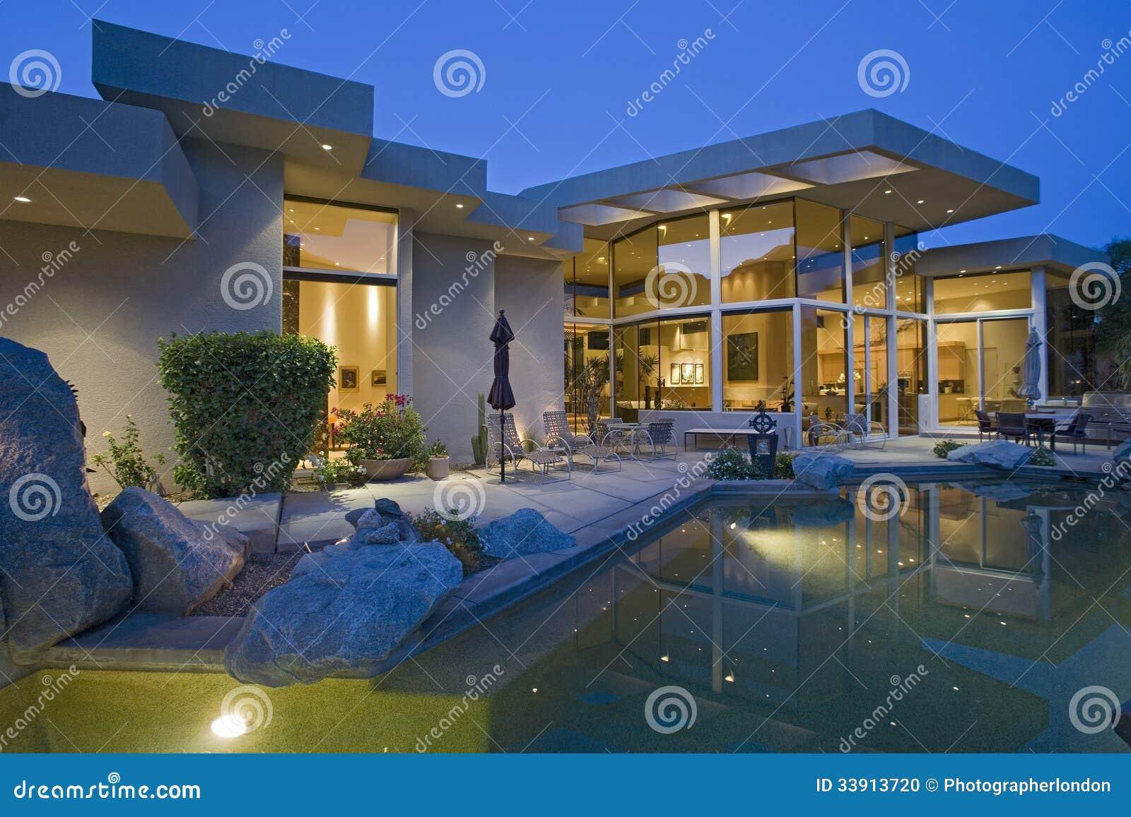 Casa con la piscina en patio trasero en la oscuridad foto for Piscinas en el patio de la casa