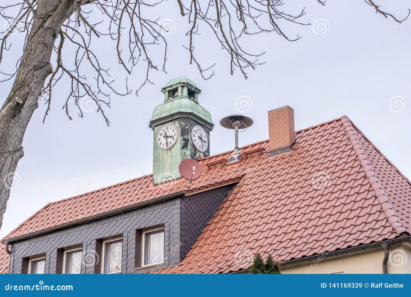 Casa con la torre de reloj y la sirena del cuerpo de bomberos local en el tejado