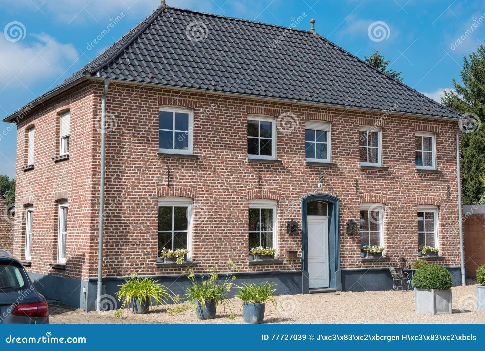 Casa con mattoni a vista rossa con le finestre bianche e l for Finestre bianche