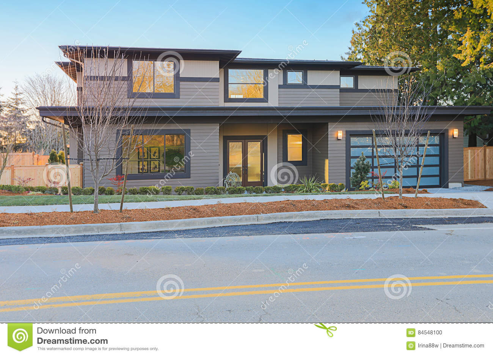 Casa da construção nova com o baixo telhado da inclinação e o tapume marrom