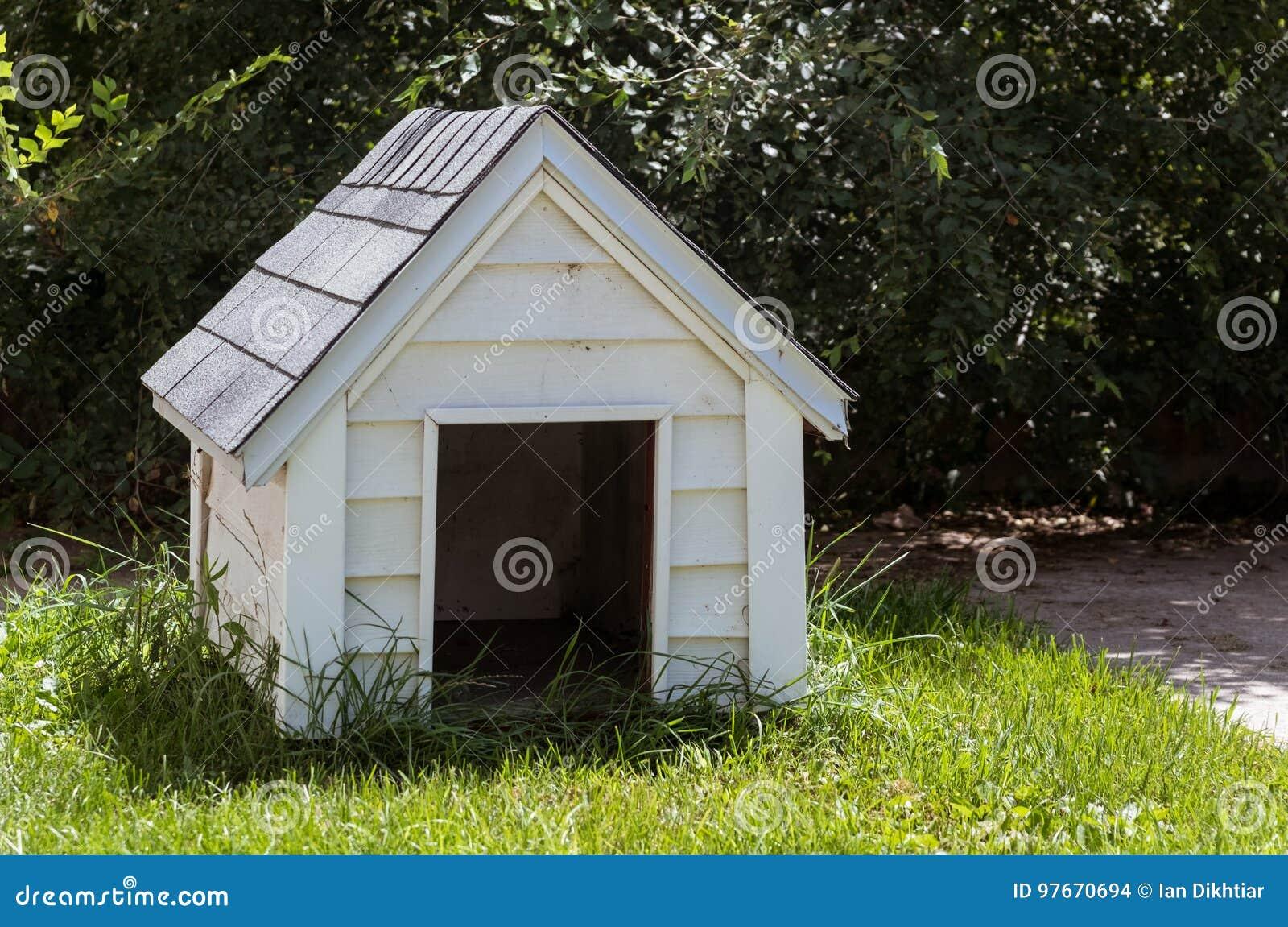 Casa de cachorro de madeira branca em um quintal da casa
