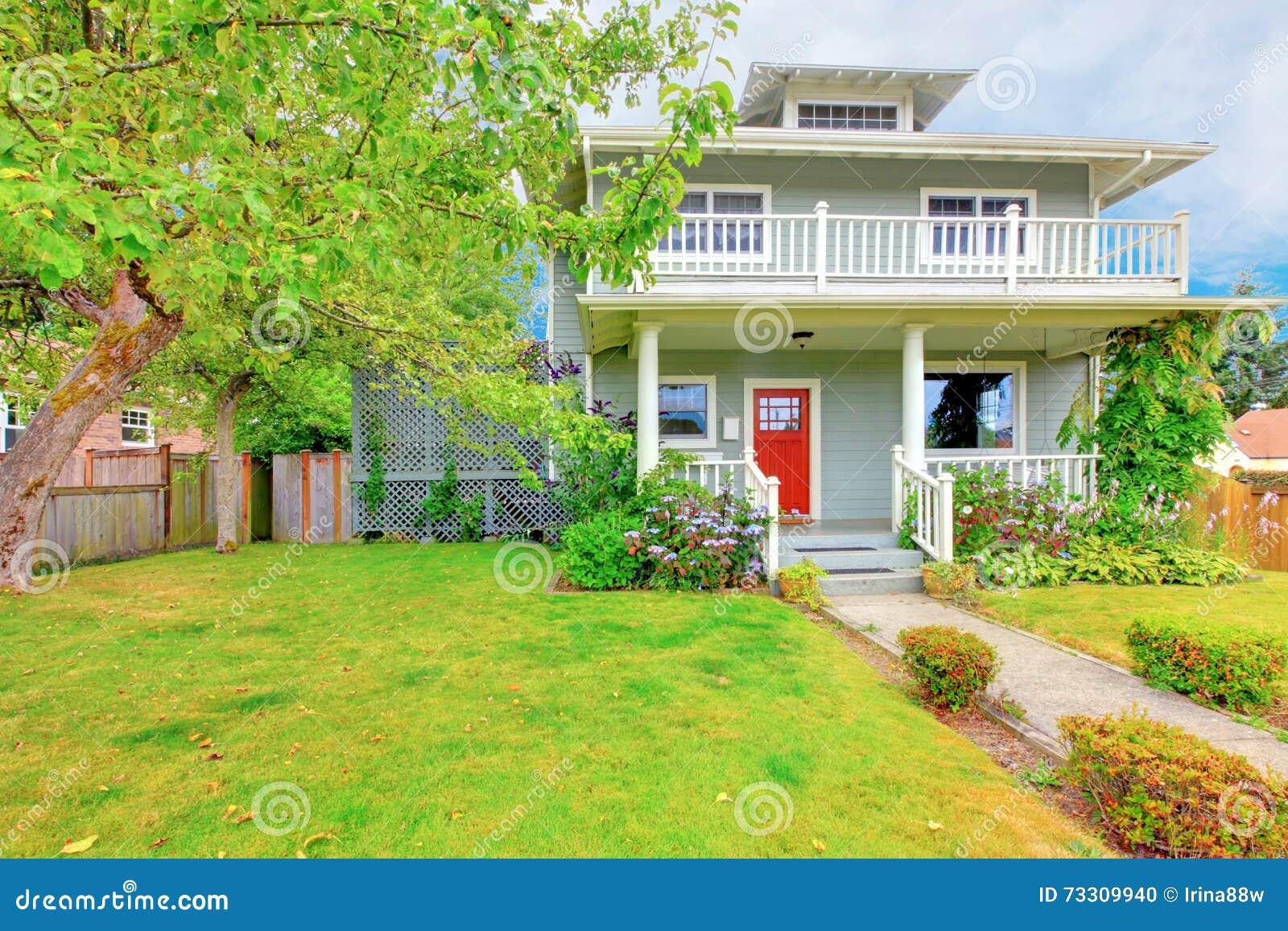 Casa de dois níveis verde americana exterior com guarnição branca e a porta de entrada vermelha