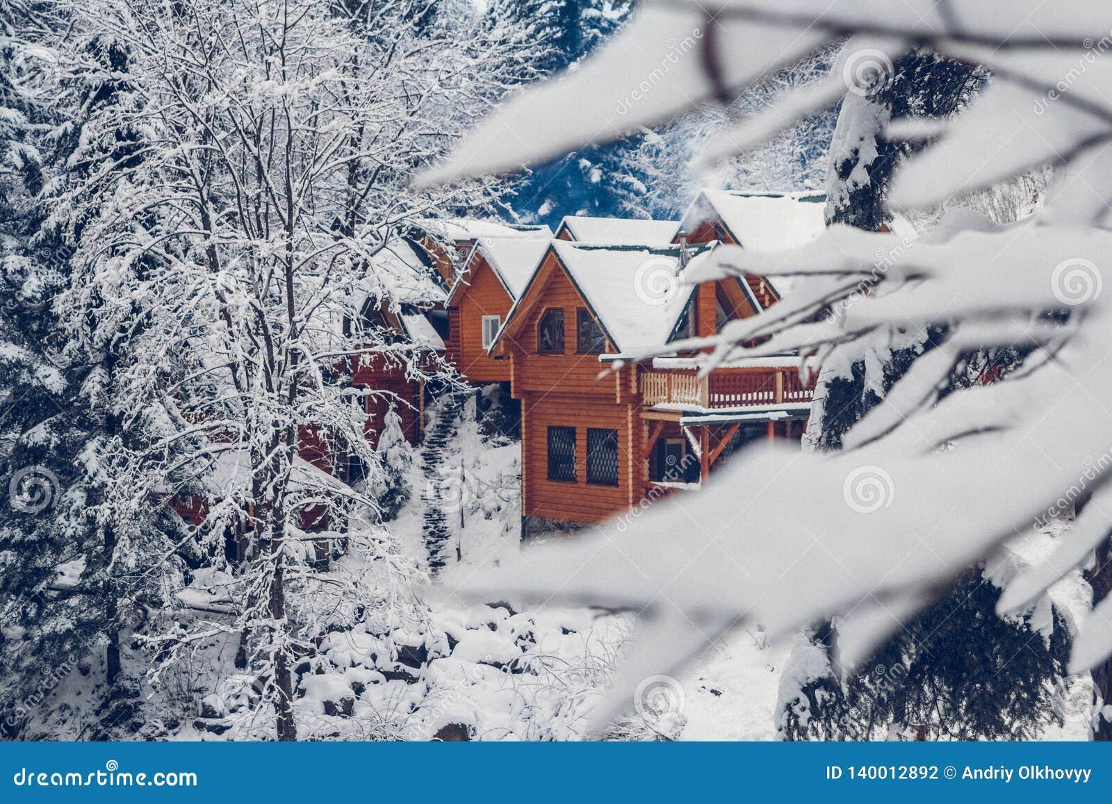 A casa de férias de madeira da casa de campo no recurso de feriado da montanha cobriu com a neve fresca no inverno