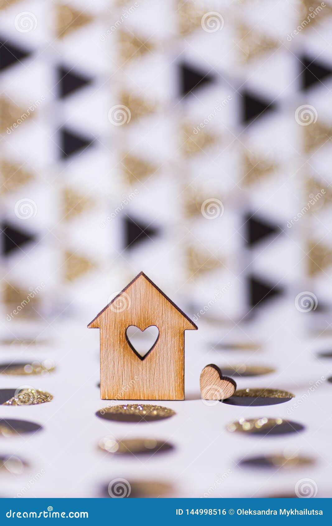 Casa de madeira do close up com furo no formulário do coração no fundo abstrato geométrico com brilho dourado