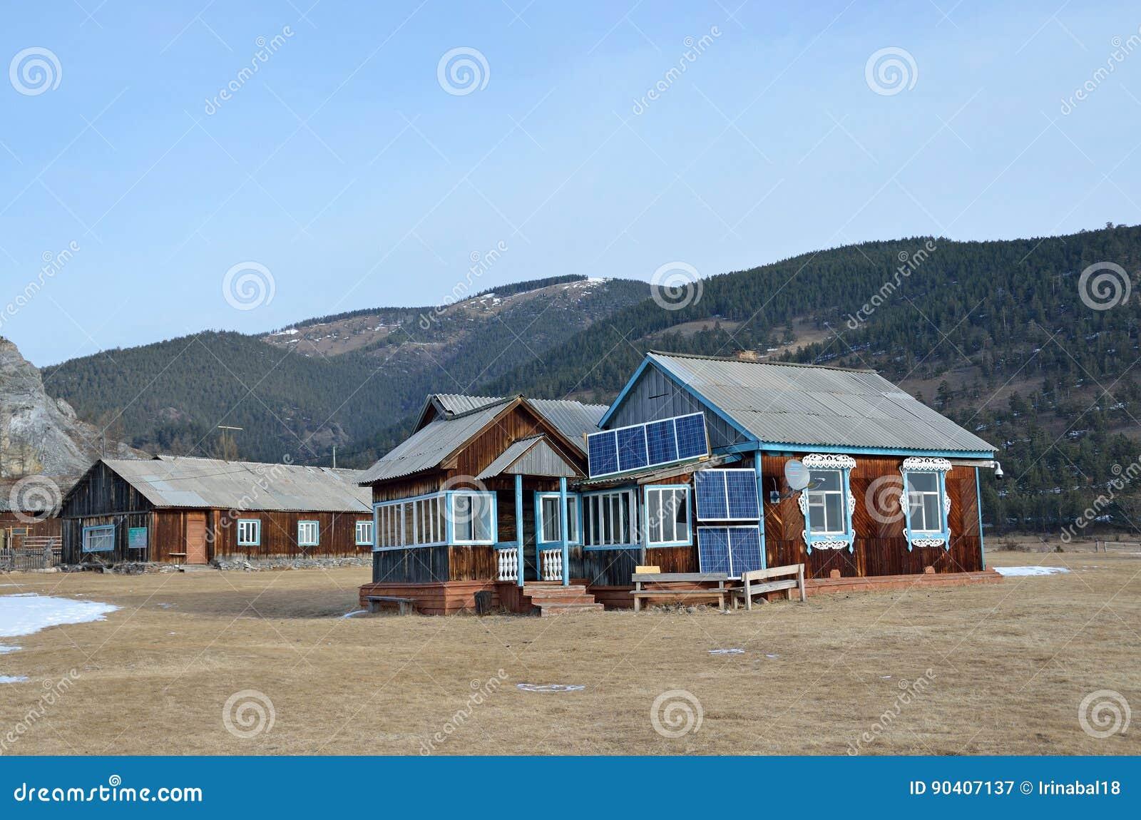 Casa de madeira em uma manhã do inverno na costa do Lago Baikal perto do cabo Bolshoy Kadilniy