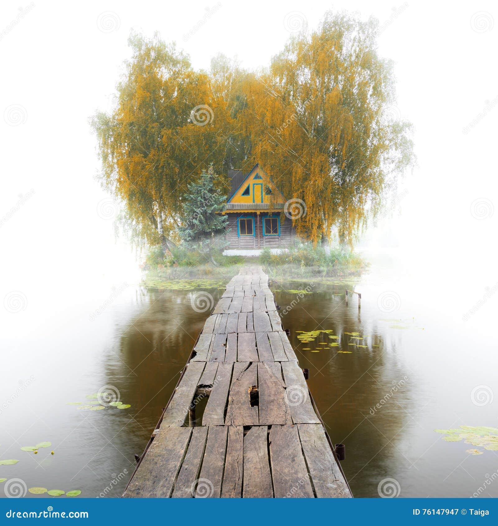 Casa de madeira velha no lago, manhã nevoenta do outono