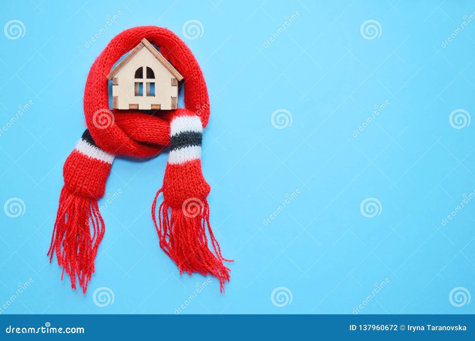 Casa de madera con las ventanas en una bufanda roja en un fondo azul, casa caliente, aislamiento del juguete de la casa, copyspac