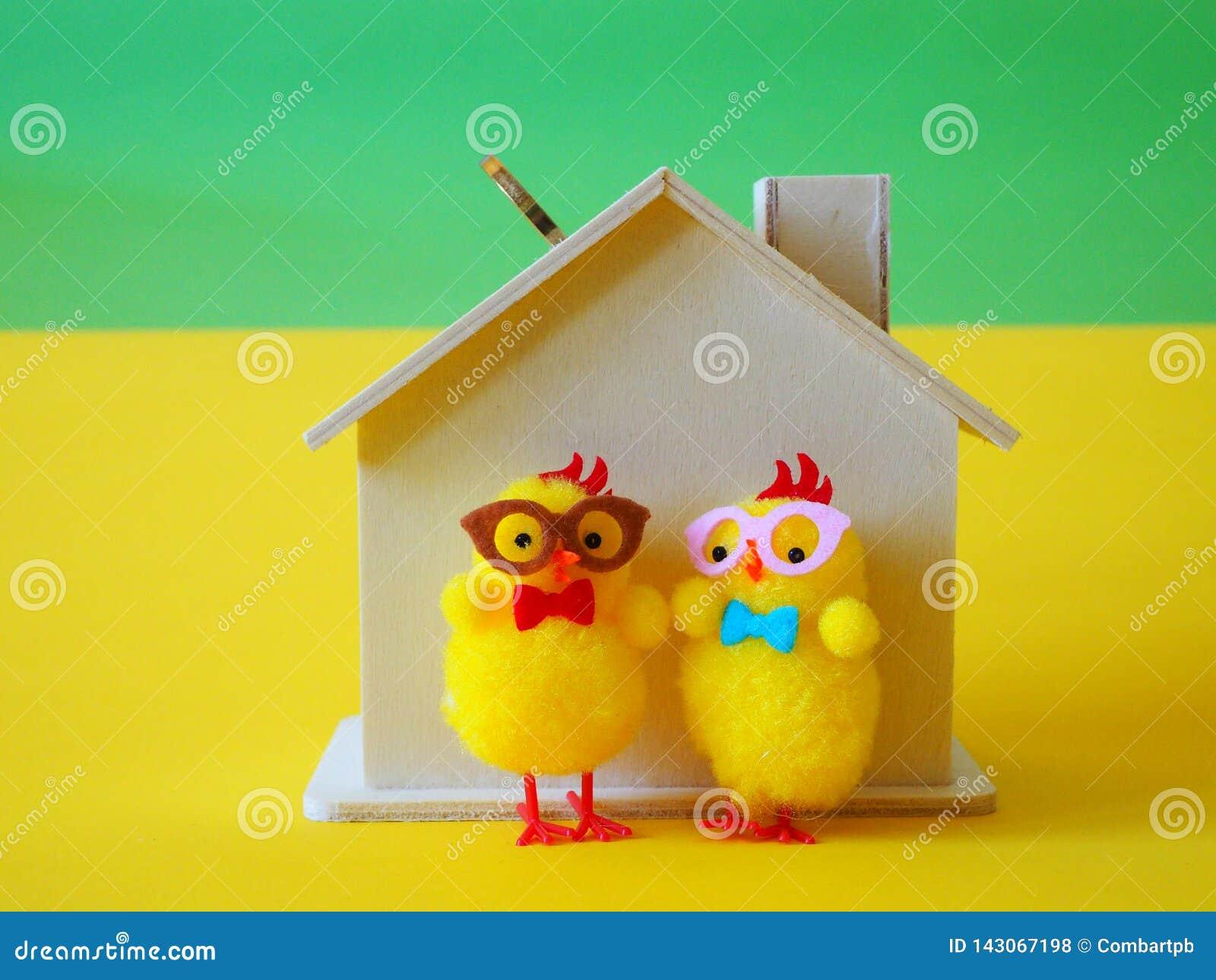 Casa de madera de la hucha con las monedas y los pollos