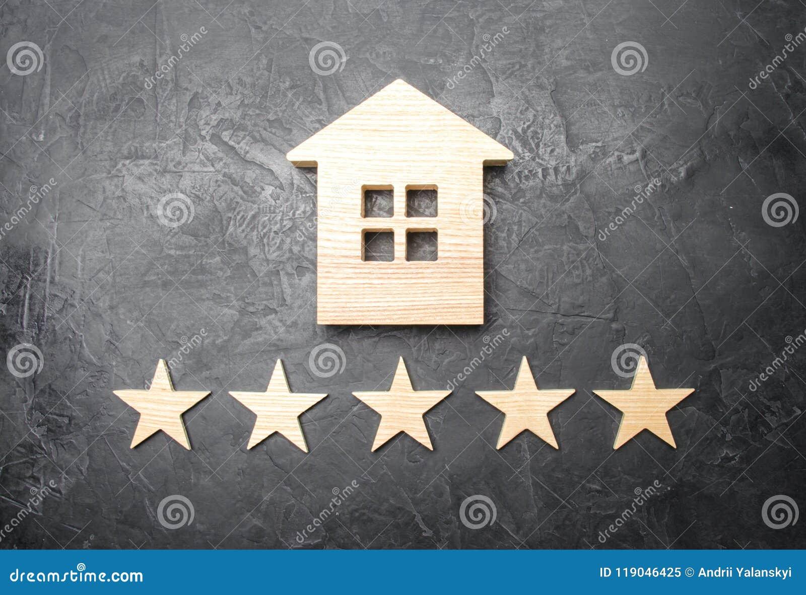 Casa de madera y cinco estrellas en un fondo gris Grado de casas y de la propiedad privada Comprando y vendiendo, alquilando los