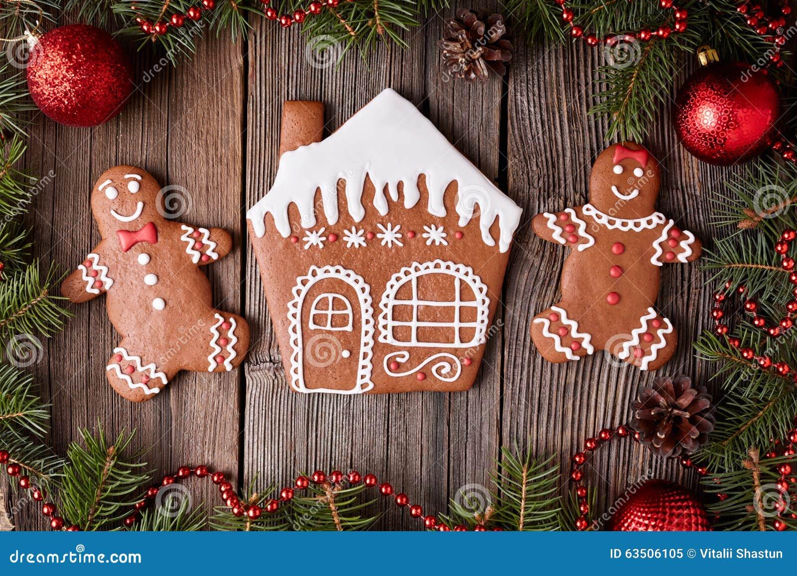 Casa de pão-de-espécie, homem e Natal das cookies da mulher