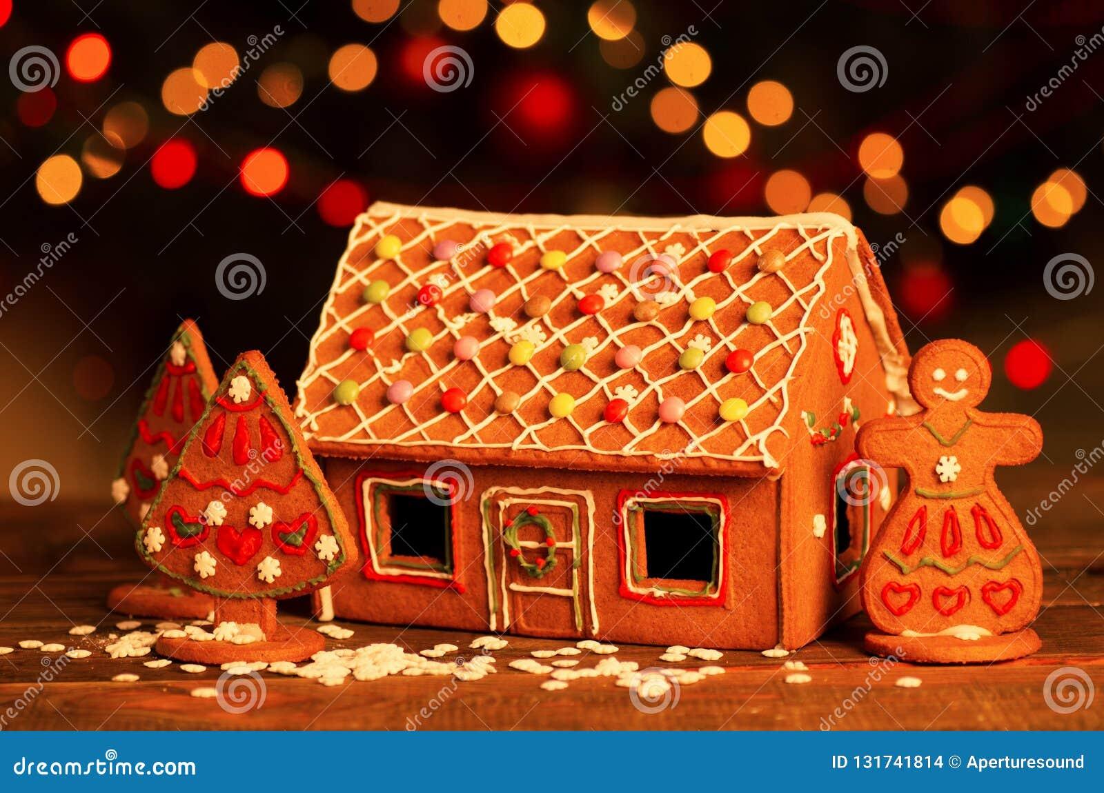 Casa de pão-de-espécie caseiro do Natal em uma tabela Luzes da árvore de Natal no fundo