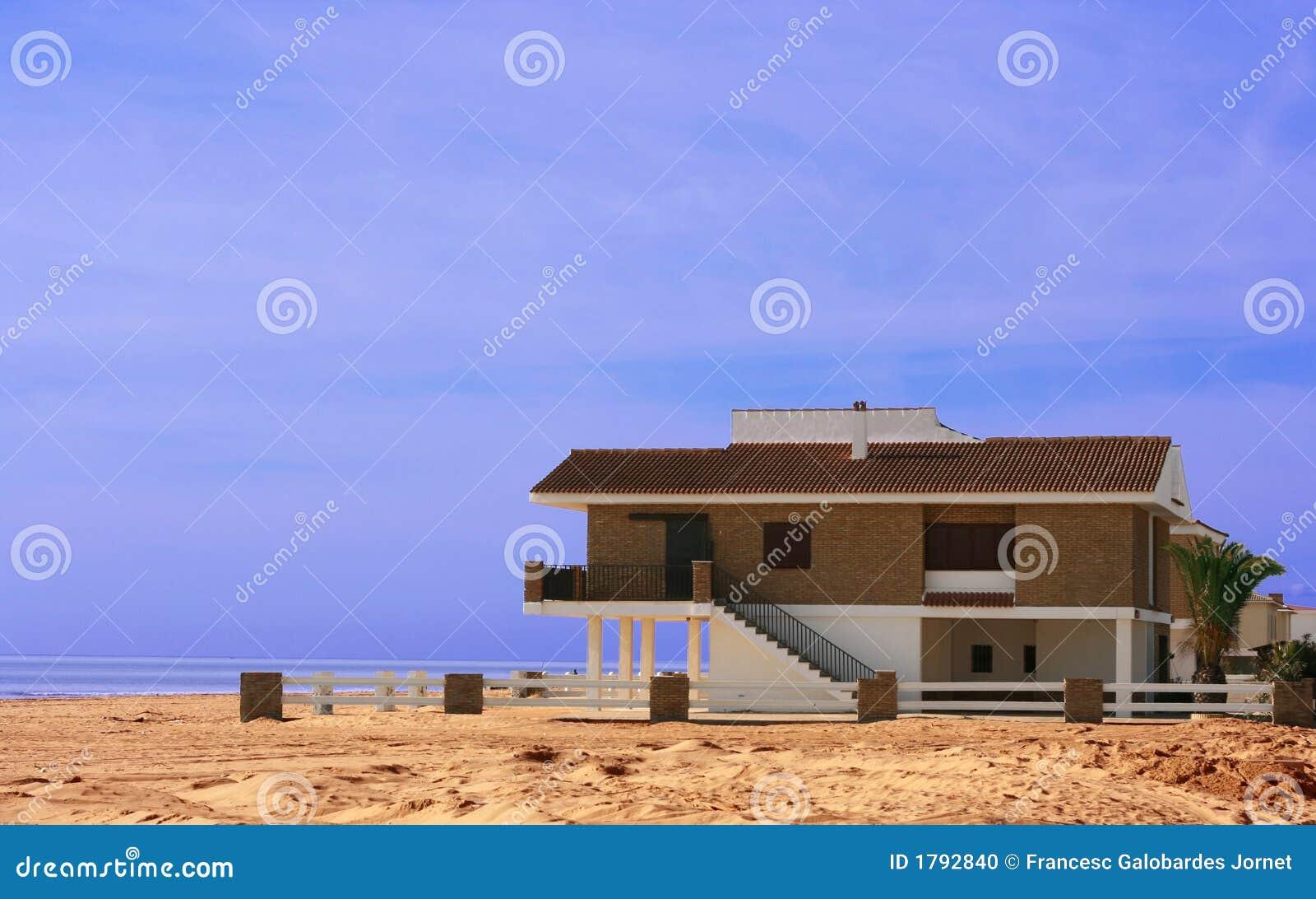 Casa de playa que se sienta en la arena foto de archivo for Arena de playa precio