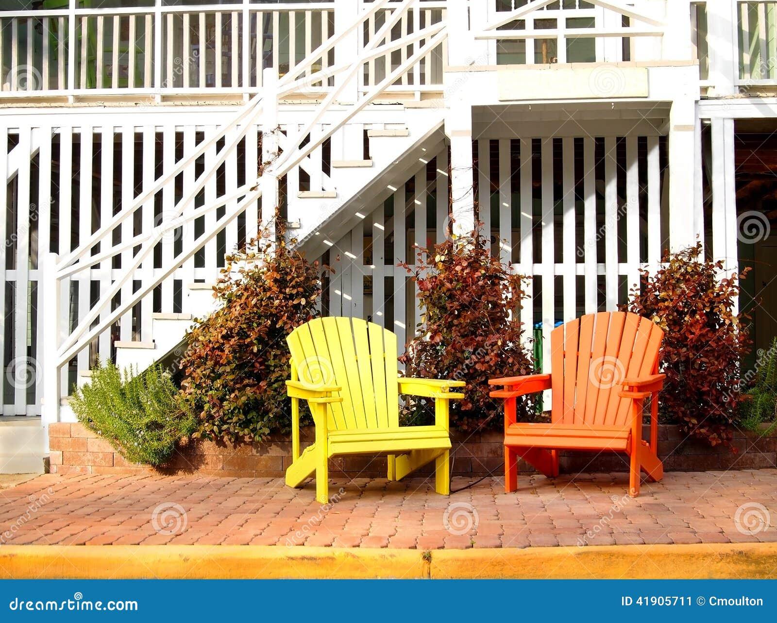 Um par de cadeiras de madeira do adirondack de um amarelo e de uma  #C12E0A 1300x1059