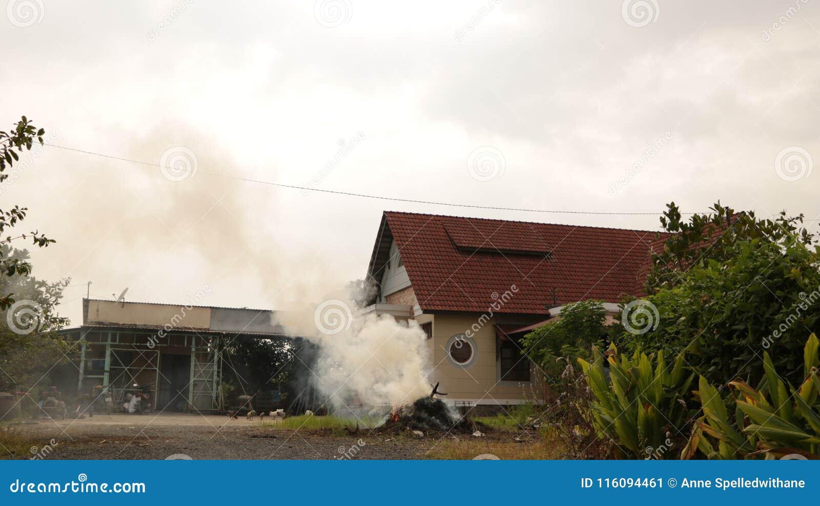 Casa del campo del vintage con la pila ardiente de paja en jardín
