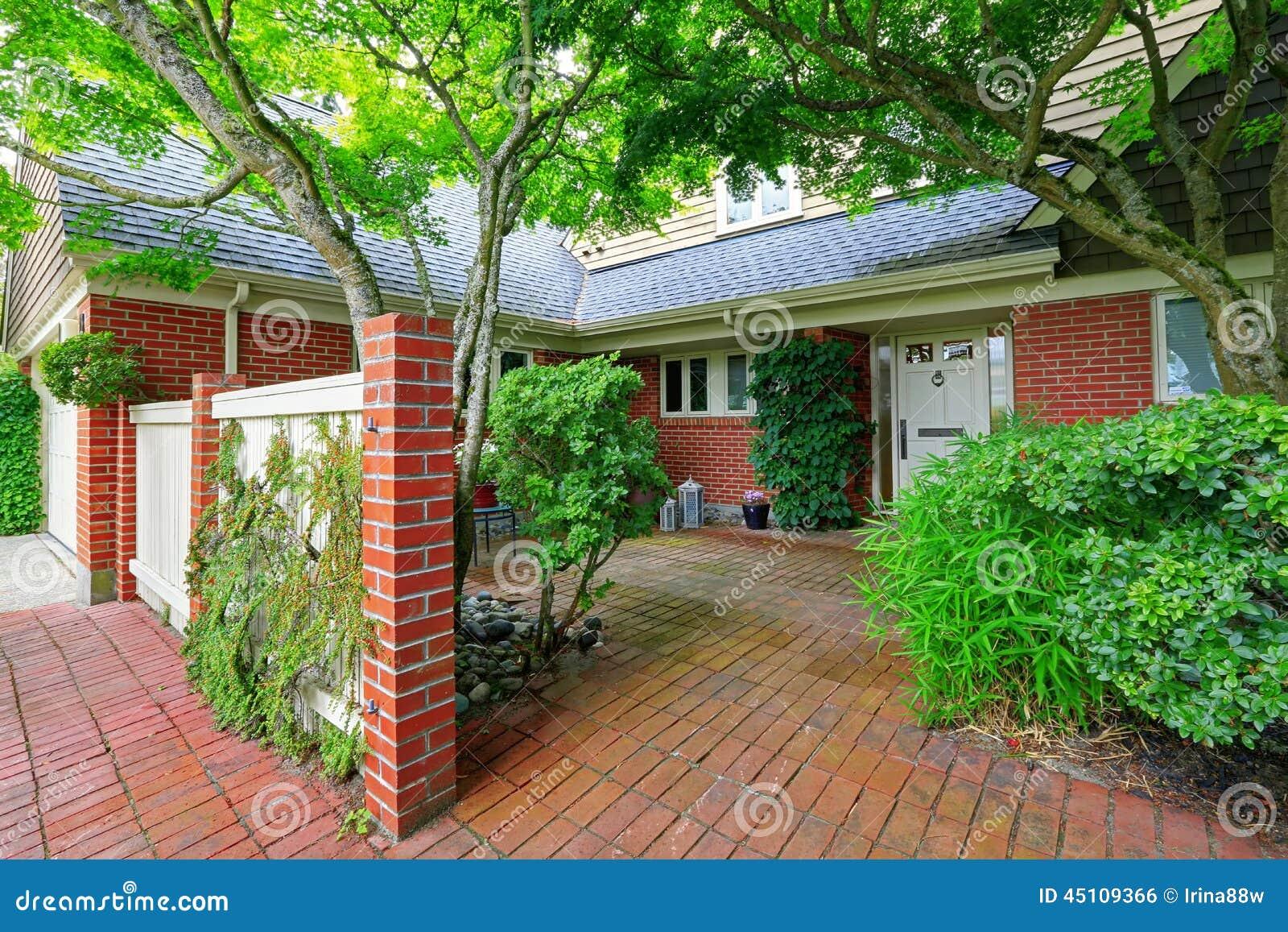 Casa Del Ladrillo Exterior Con El Jardín Del Suelo De Baldosas Foto ...
