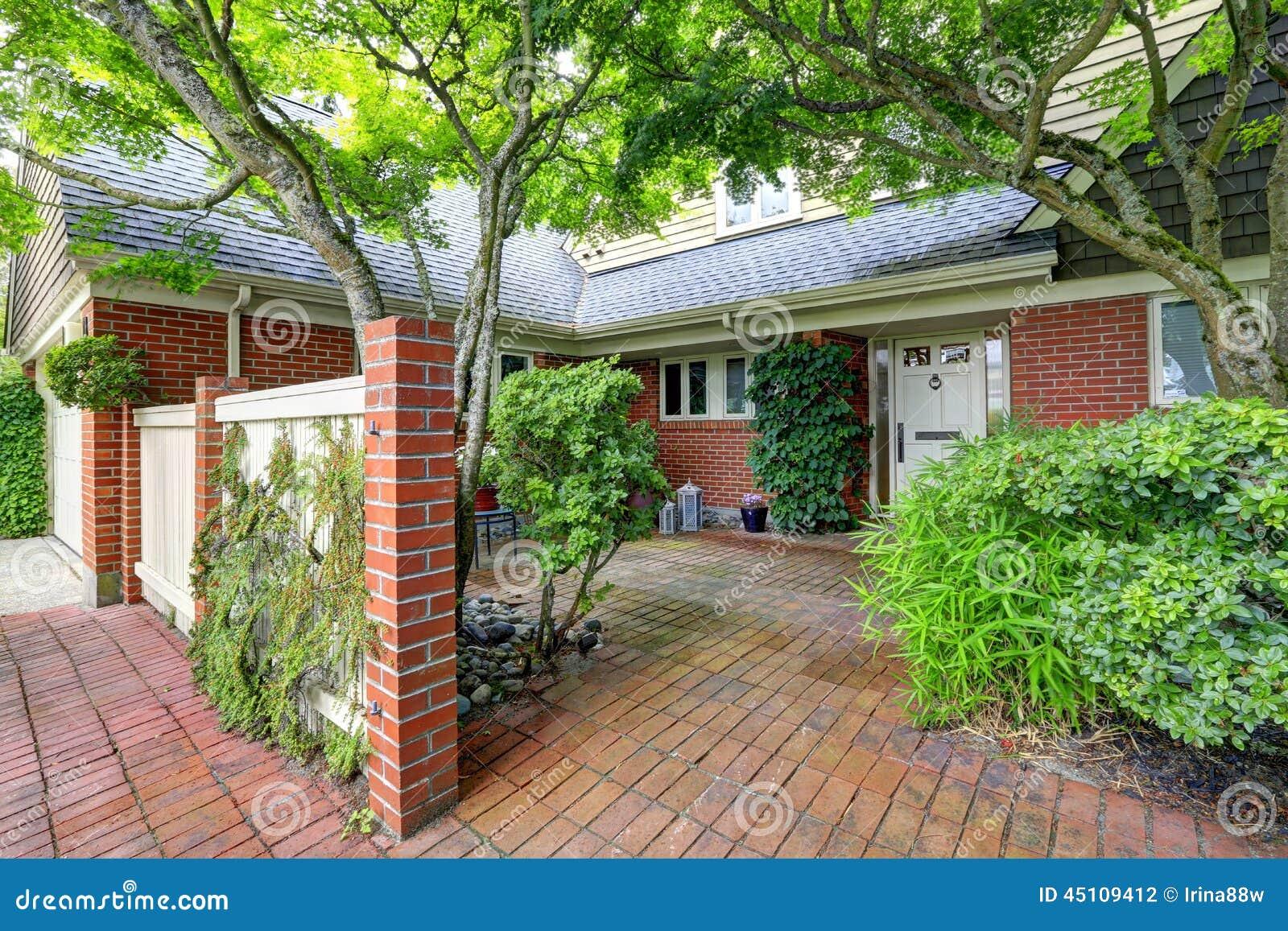 Casa del ladrillo exterior con el jard n del suelo de baldosas - Suelos jardin exterior ...