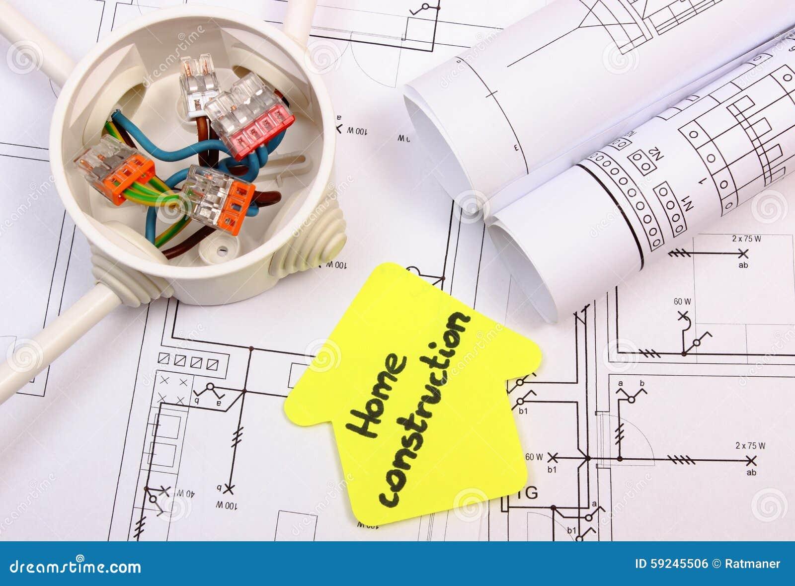 Casa del papel amarillo, de la caja eléctrica con los cables y del dibujo de construcción