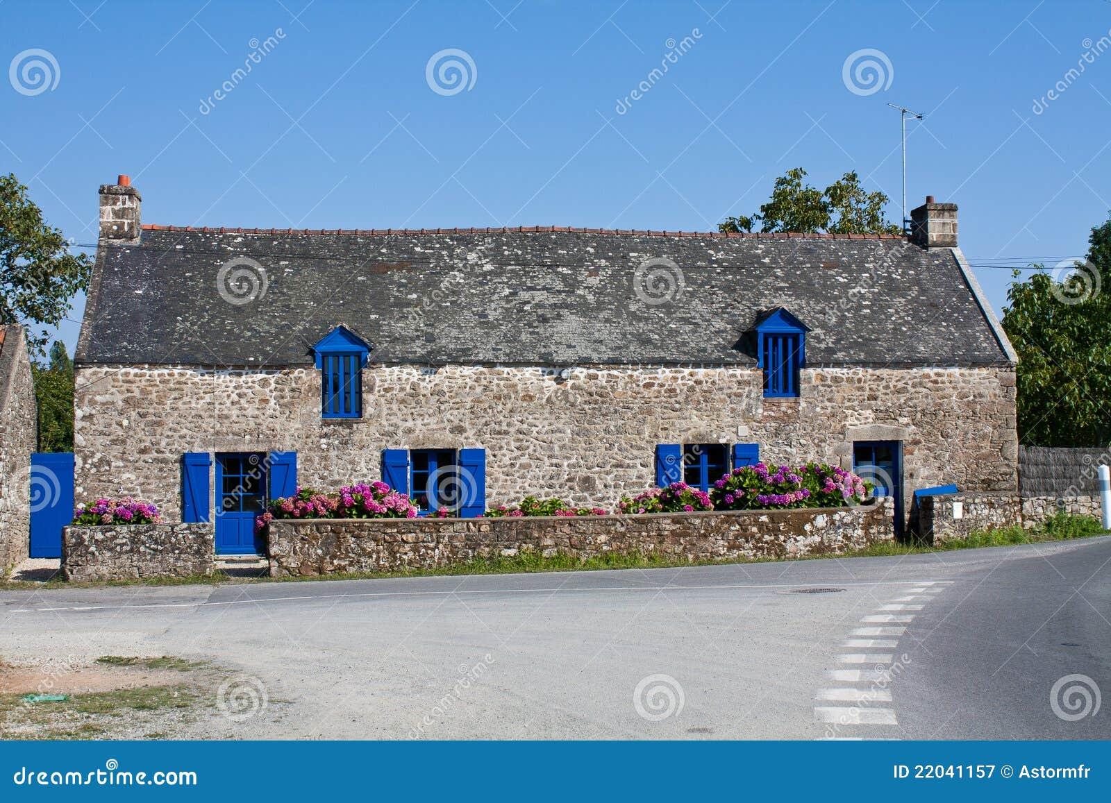 Casa di campagna tipica con gli otturatori blu in Brittany, Francia.