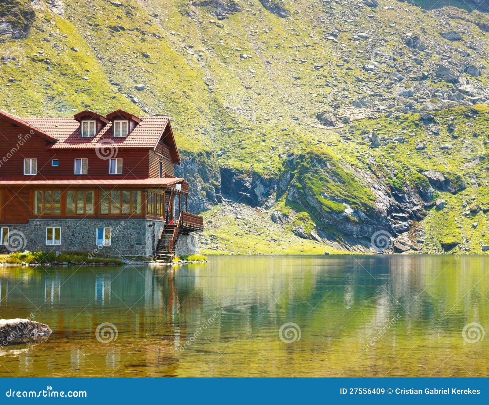Casa di legno rossa sul lago del ghiacciaio immagini stock for Affitti cabina grande lago orso