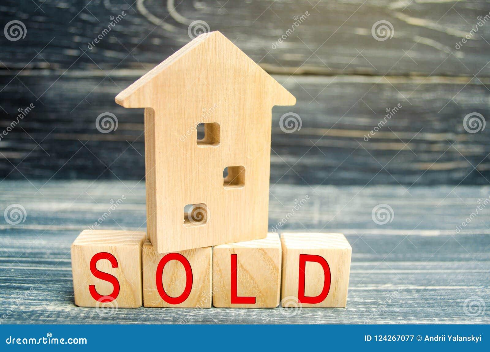 Casa di legno su un fondo nero con l iscrizione venduta vendita della proprietà, casa, bene immobile Alloggiamento acquistabile P