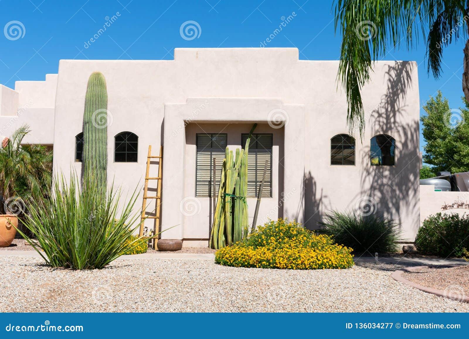 Casa do estilo de Santa Fe com o cacto no jardim da frente