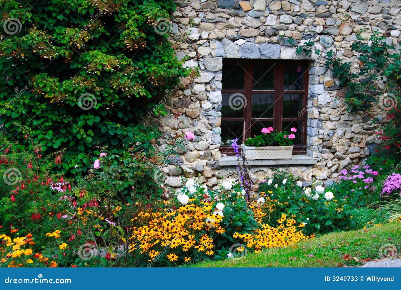 jardim pedras e flores:Indicador de uma casa pedra-construída em um jardim florescido rural.